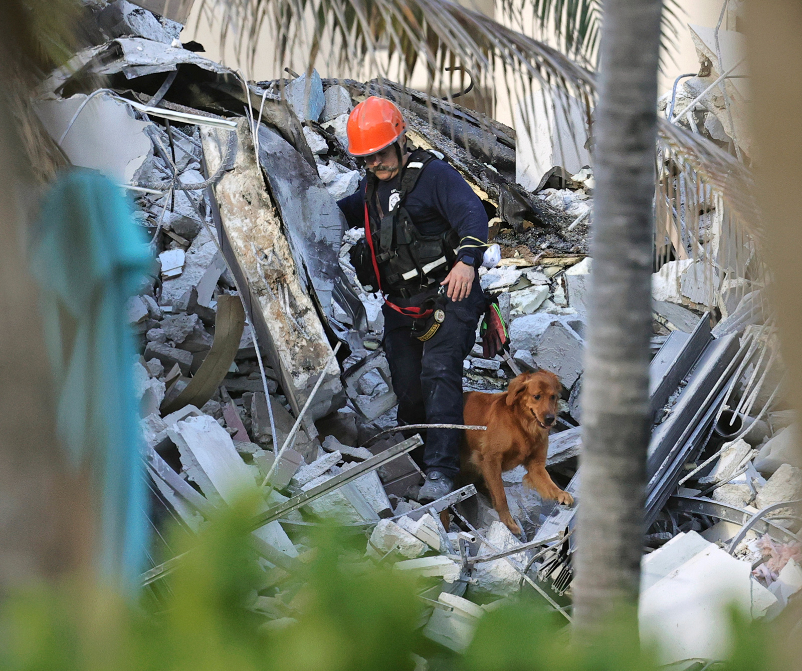 Fire rescue personnel conduct a search and rescue with dogs through the rubble of the Champlain Towers South Condo after the multistory building partially collapsed in Surfside on Thursday.