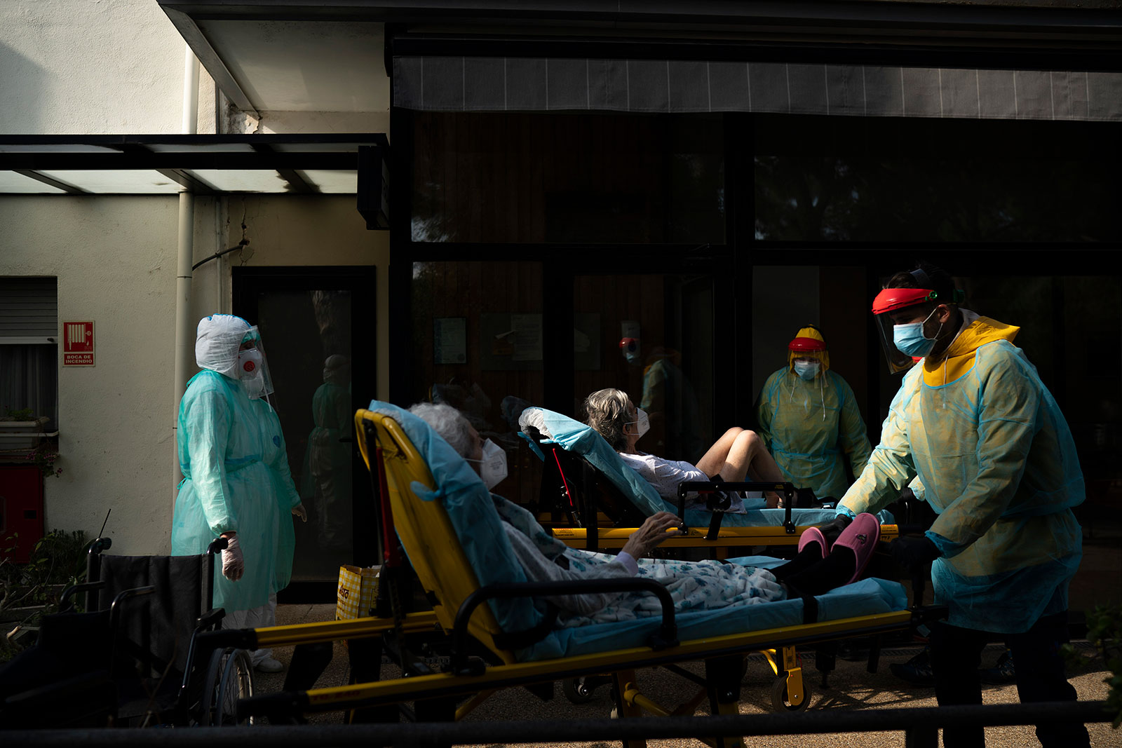 Health workers help two elderly coronavirus patients in Barcelona, Spain, on April 11.