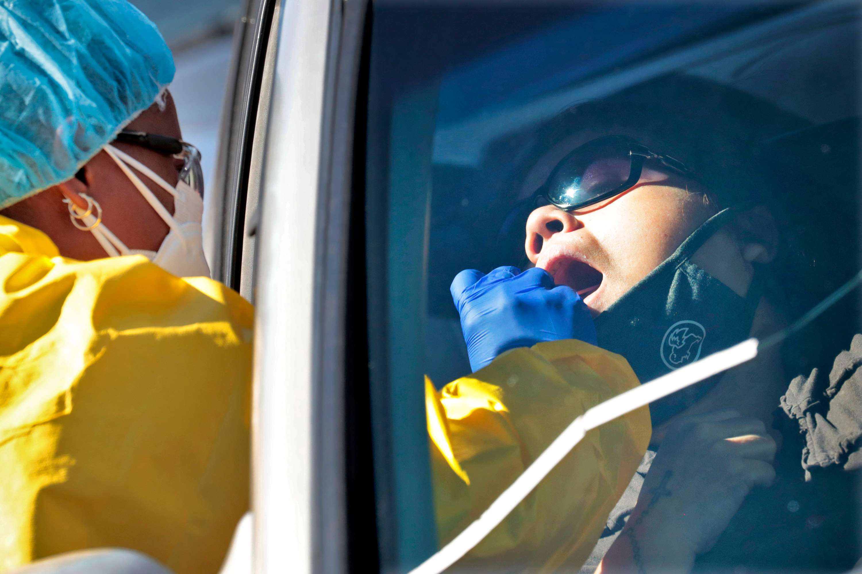 People get tested for COVID-19 at a drive through testing site hosted by the Puente Movement migrant justice organization on June 20 in Phoenix.