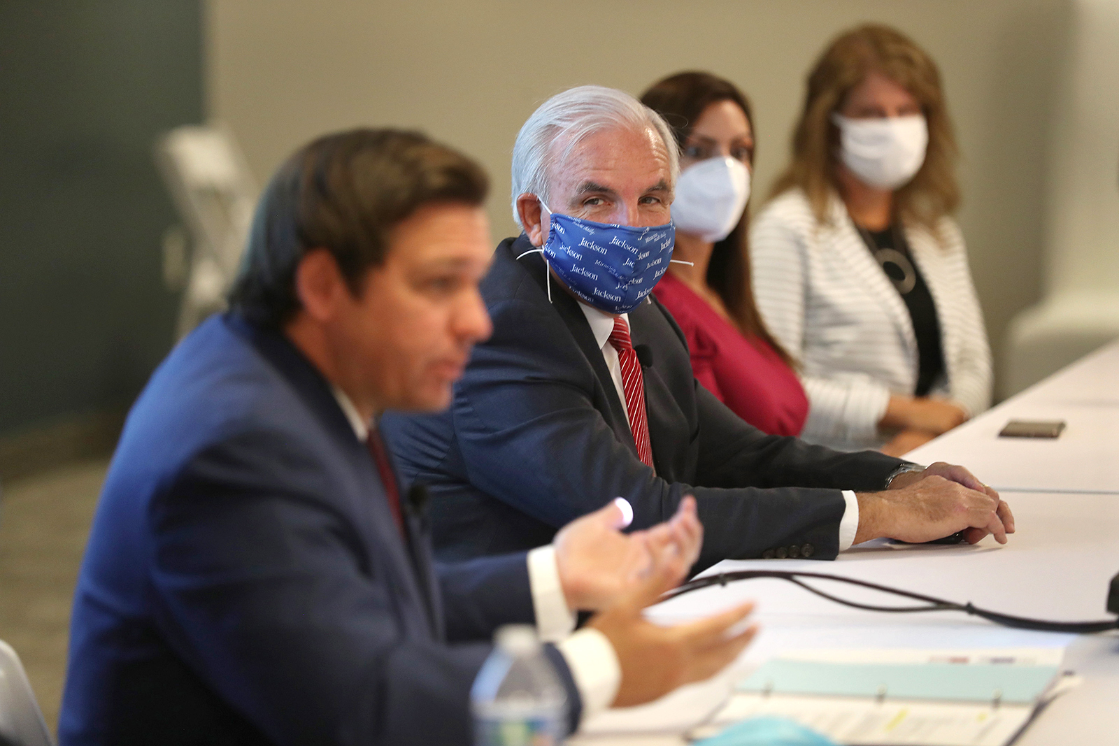 Mayor of Miami-Dade Carlos A. Gimenez (Right) listens as Florida Gov. Ron DeSantis (Left) speaks during a press conference in Miami on July 07.