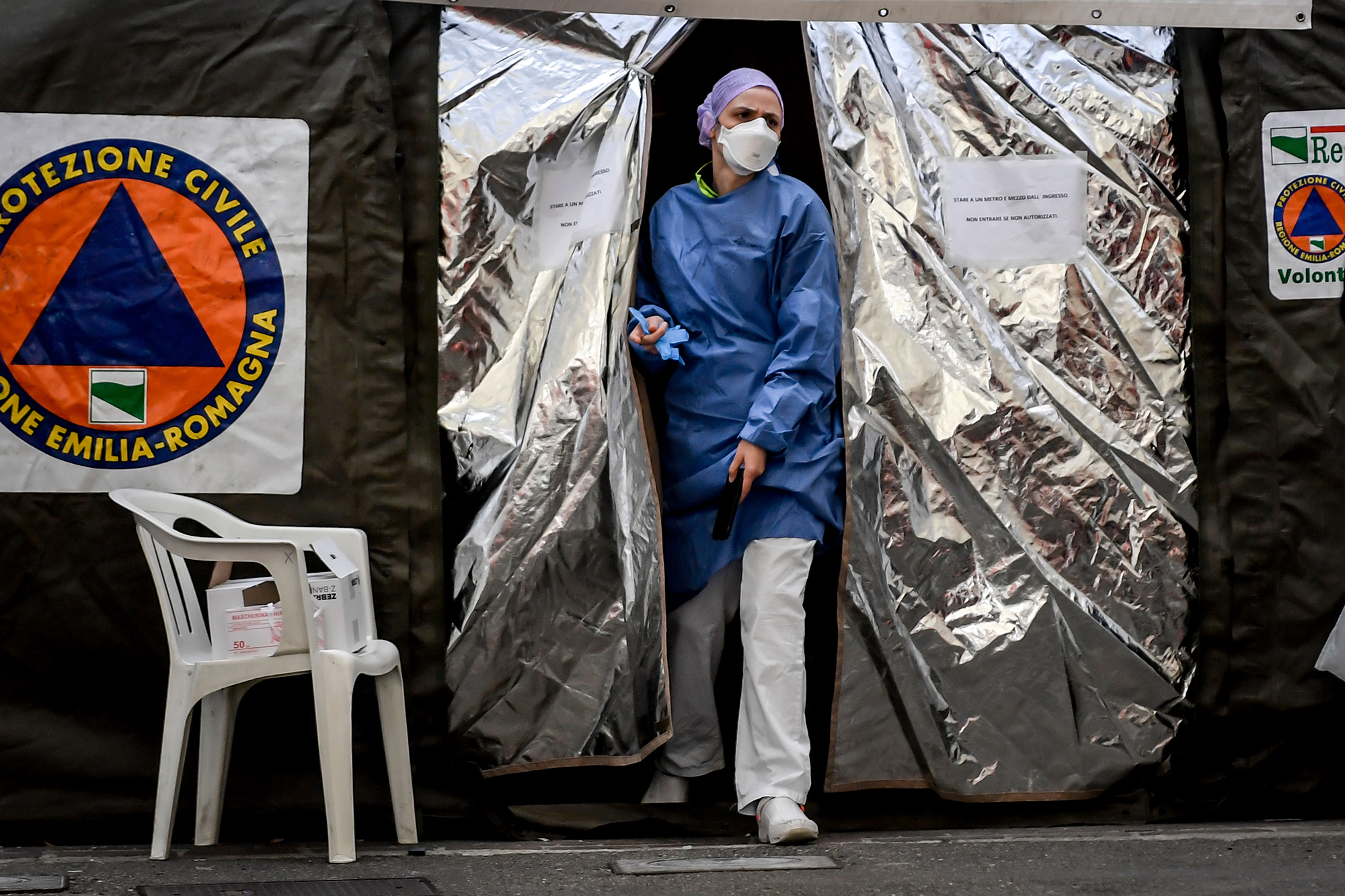 A paramedic wearing a mask gets out of a tent set up by the Italian Civil Protection outside the emergency ward of the Piacenza hospital in northern Italy on Thursday, February 27.