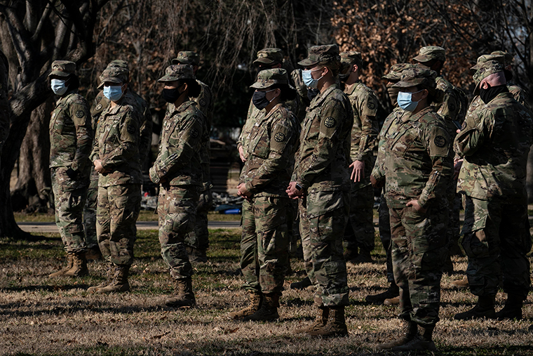 Members of the National Guard wear protective face masks and stand in a formation on the US Capitol grounds on January 22, in Washington, DC.