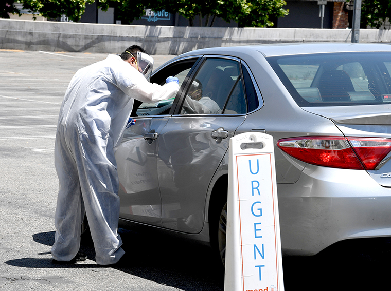 A worker performs drive-up COVID-19 testing at Mend Urgent Care testing site at the Westfield Fashion Square on May 13,  in the Sherman Oaks neighborhood of Los Angeles.