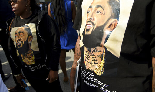 Guests wear T-shirts in tribute to Nipsey Hussle at the late rapper's memorial service on Thursday at the Staples Center in Los Angeles.