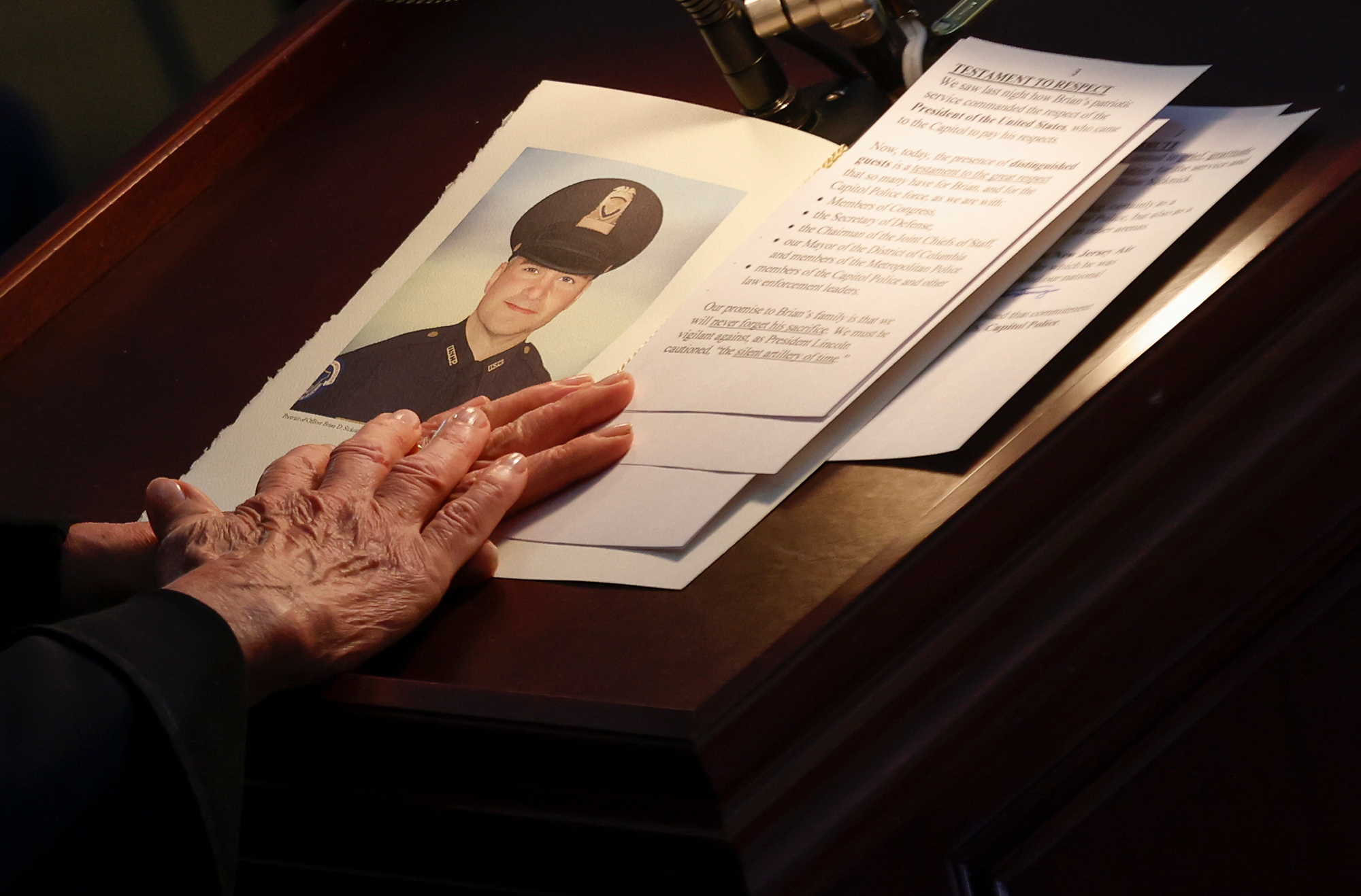 US House of Representatives Speaker Nancy Pelosi holds a portrait of late Capitol Police officer Brian Sicknick as he lies in honor during a ceremony as people pay their respects in the Rotunda of the US Capitol building on February 3, 2021, in Washington, DC.