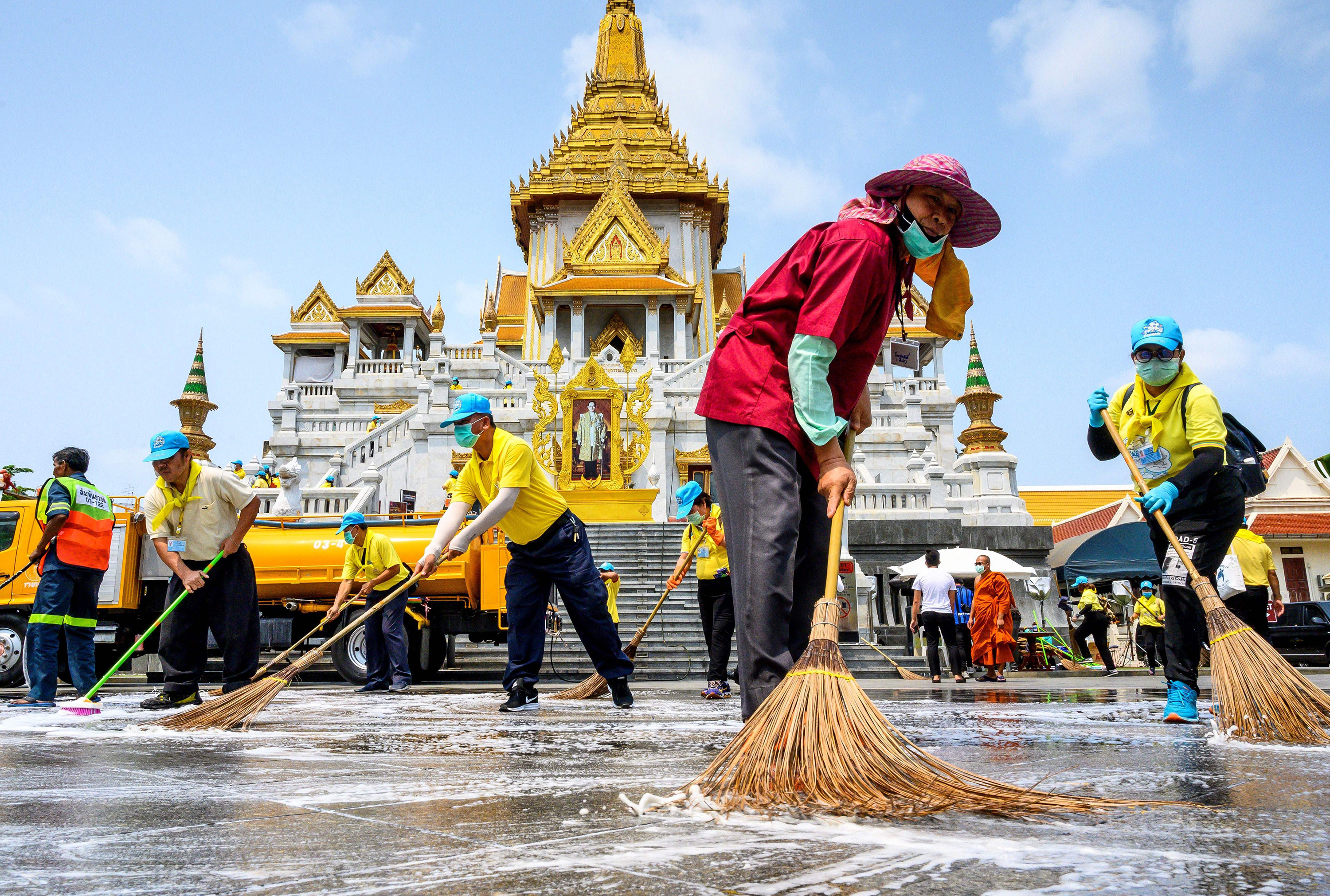 Volunteers use disinfectant Wat Traimit temple in Bangkok, Thailand on March 18.