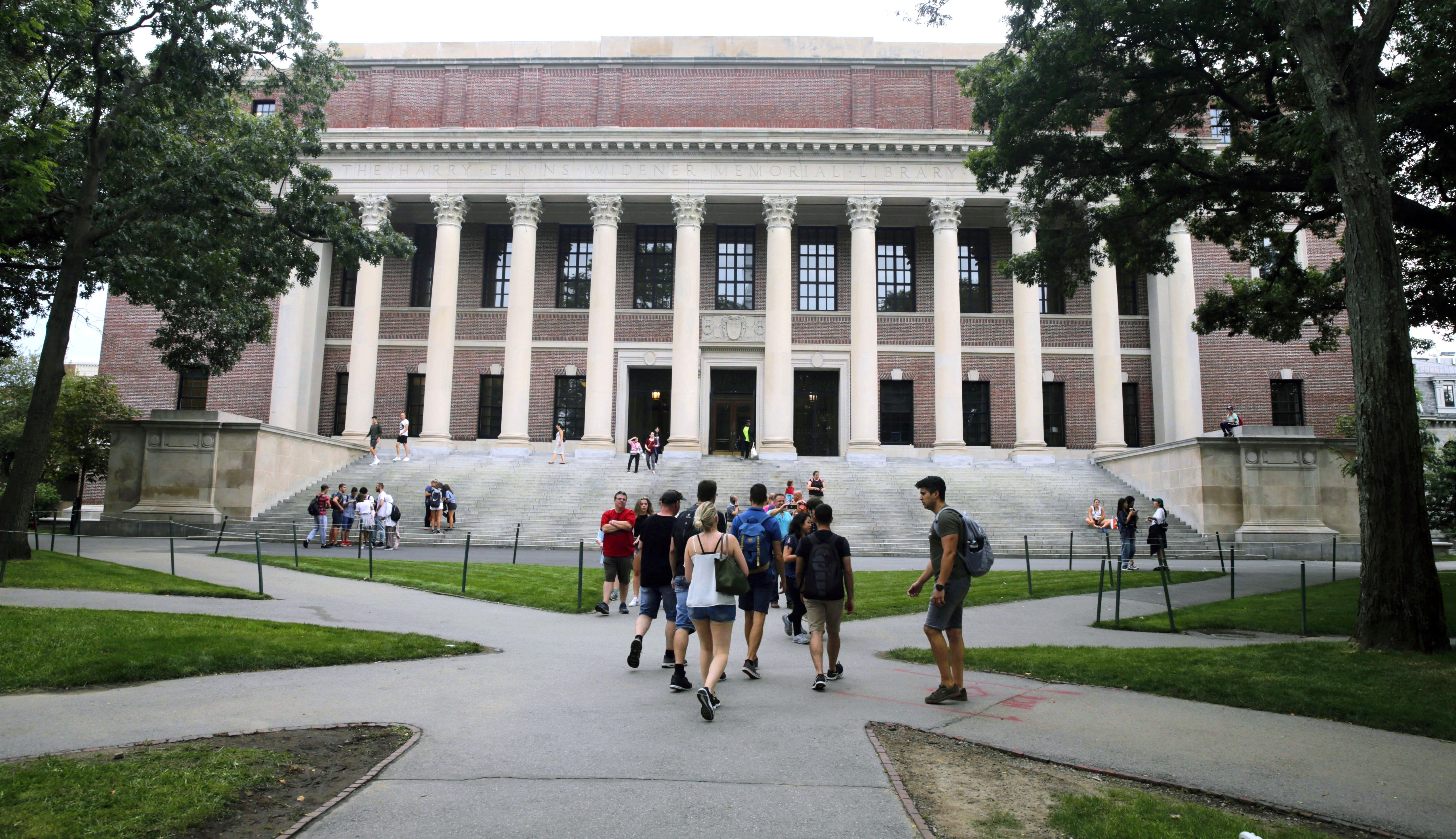 Students walk near the Widener Library in Harvard Yard at Harvard University on August 13, 2019.