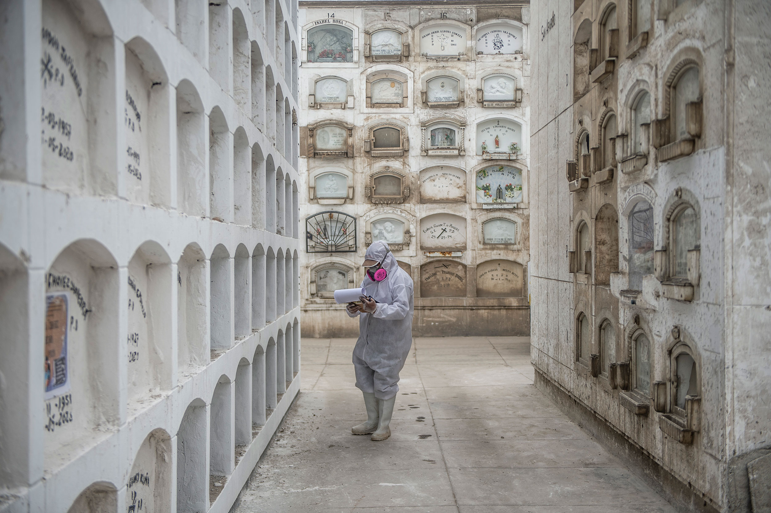 A worker checks for the names of coronavirus victims at El Angel cemetery in Lima, Peru, on May 21.