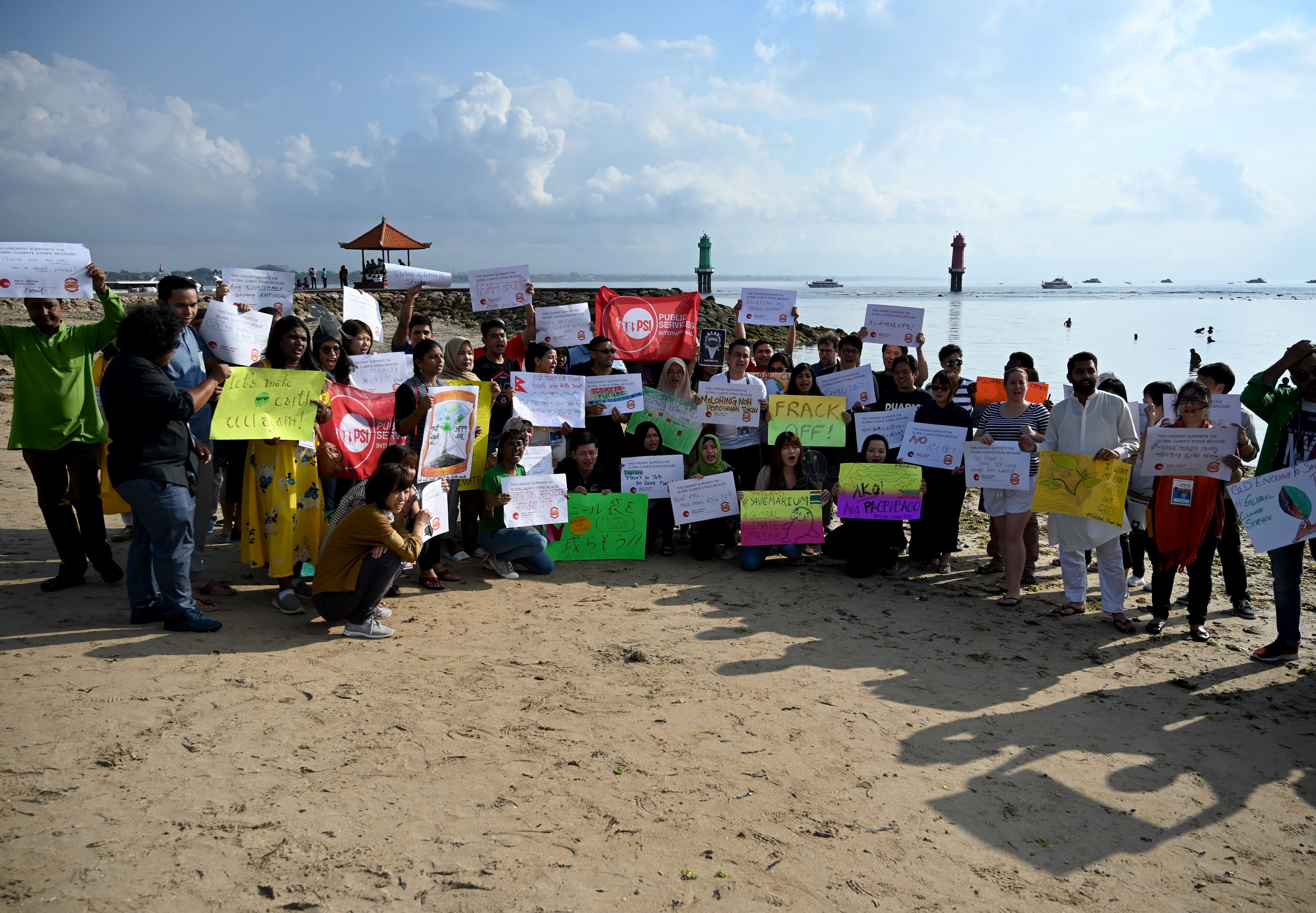People hold a rally as part of a global climate change campaign at Sanur Beach in Bali, Indonesia.