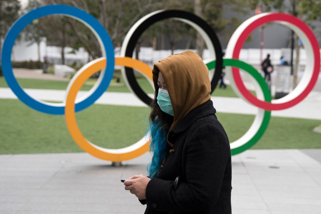 A woman wearing a face mask walks past the Olympic rings in front of the new National Stadium, the main stadium for the upcoming Tokyo 2020 Olympic and Paralympic Games, on February 26, 2020 in Tokyo, Japan.