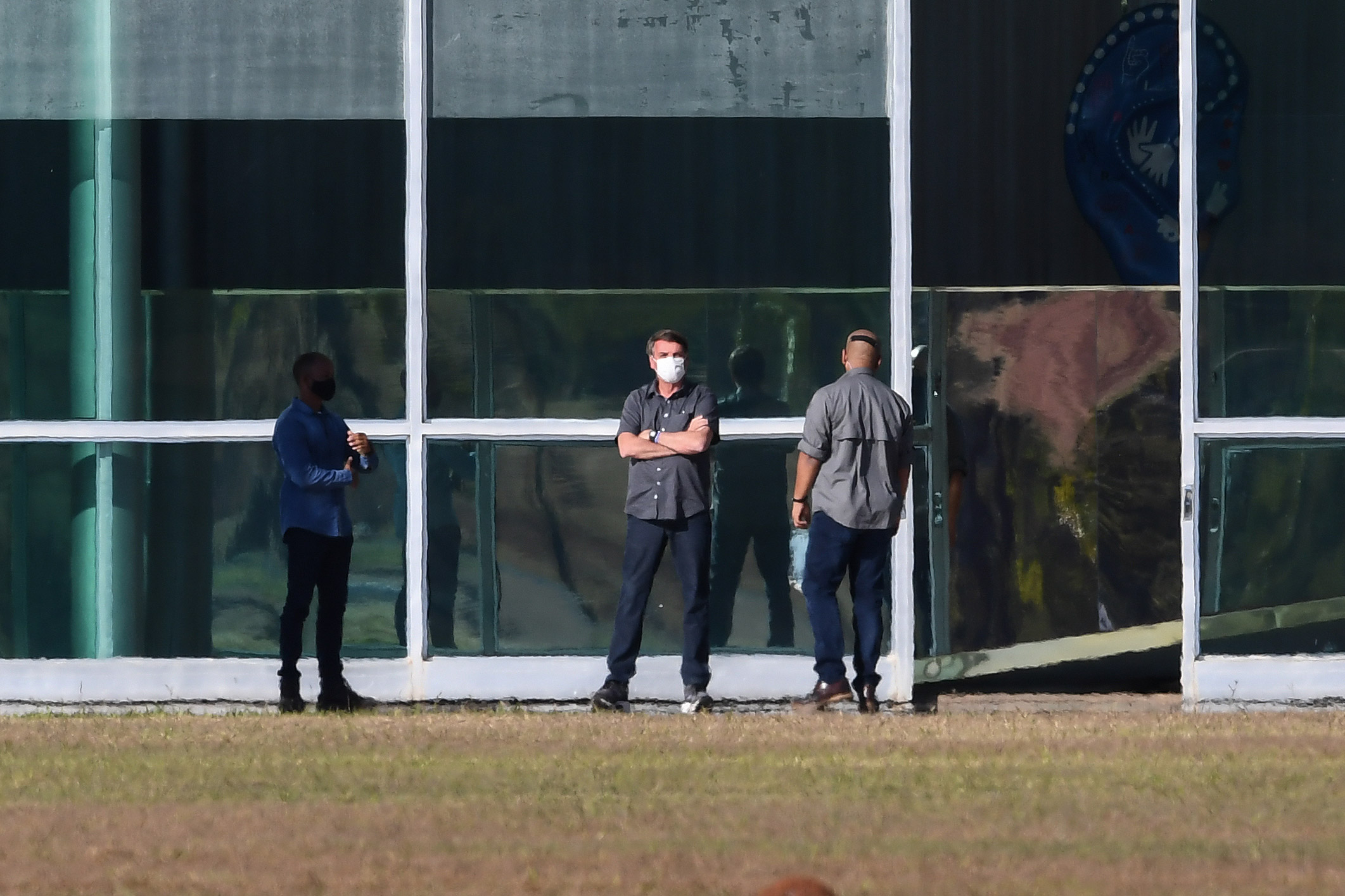 Brazilian President Jair Bolsonaro, center, is seen outside the Alvorada Palace in Brasilia, Brazil, on July 10.