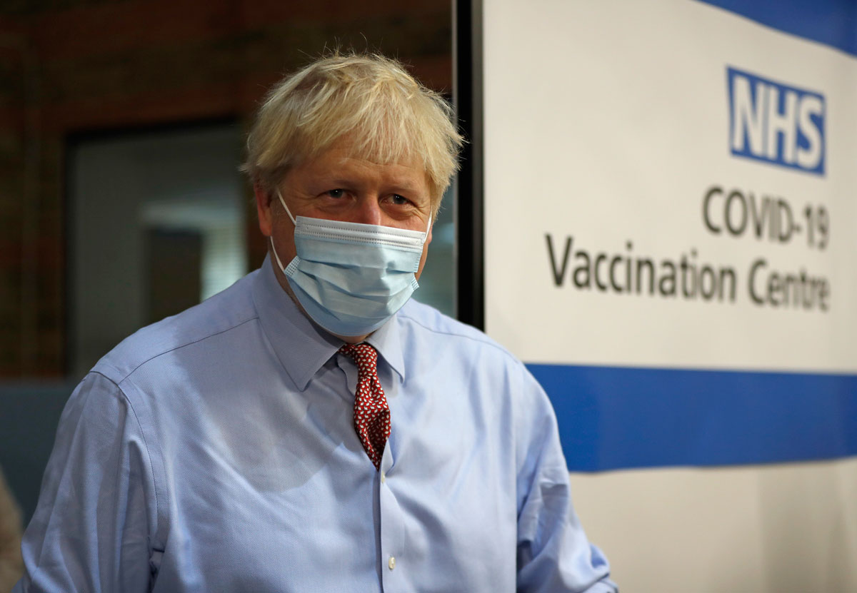 British Prime Minister Boris Johnson looks on after nurse Rebecca Cathersides administered the Pfizer-BioNTech COVID-19 vaccine to Lyn Wheeler at Guy's Hospital in London on Tuesday, December 8.