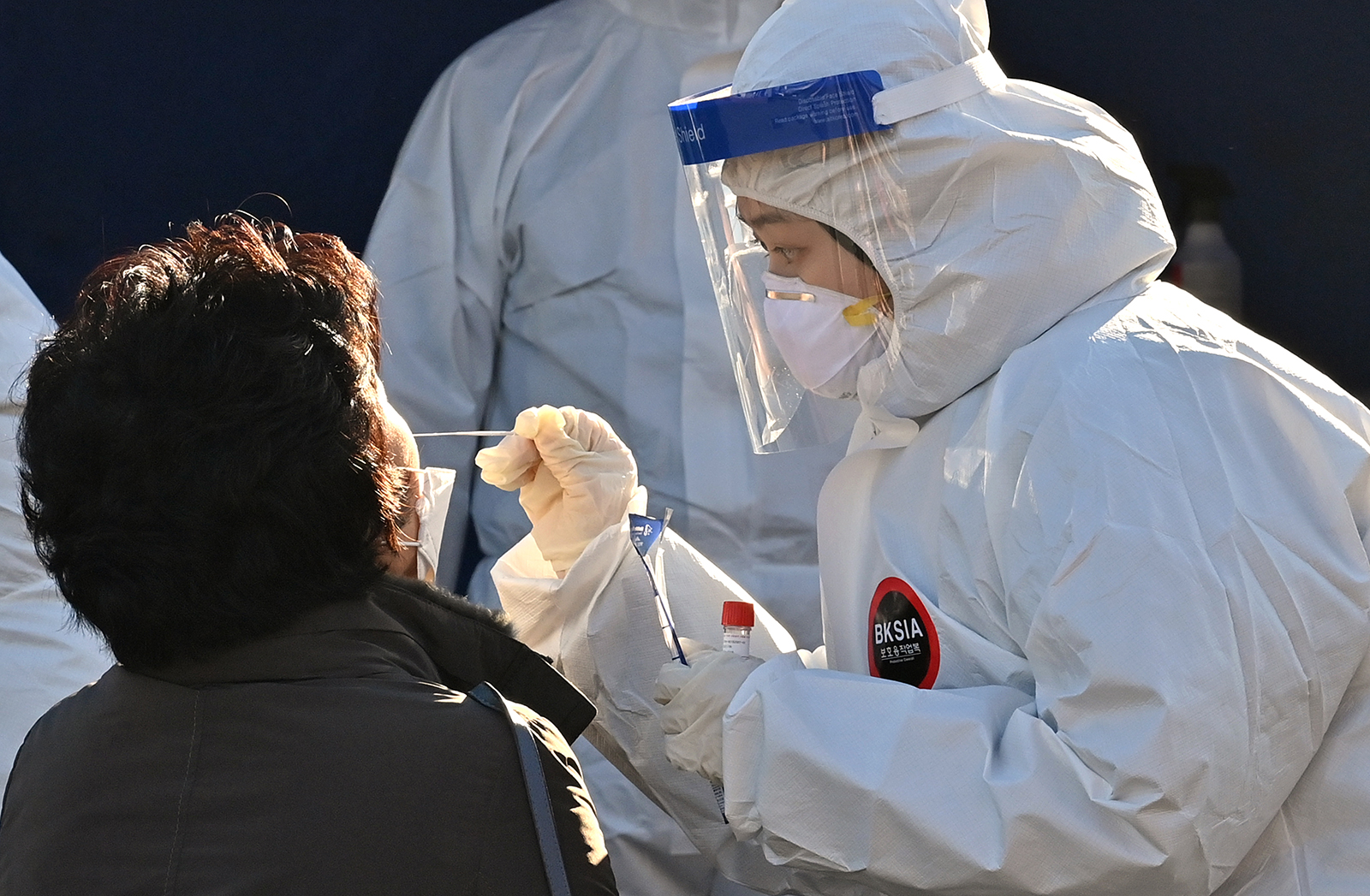 A medical staff member wearing protective gear takes a swab from a woman to test for Covid-19 at a temporary testing station in Seoul, South Korea, on Dec. 14.