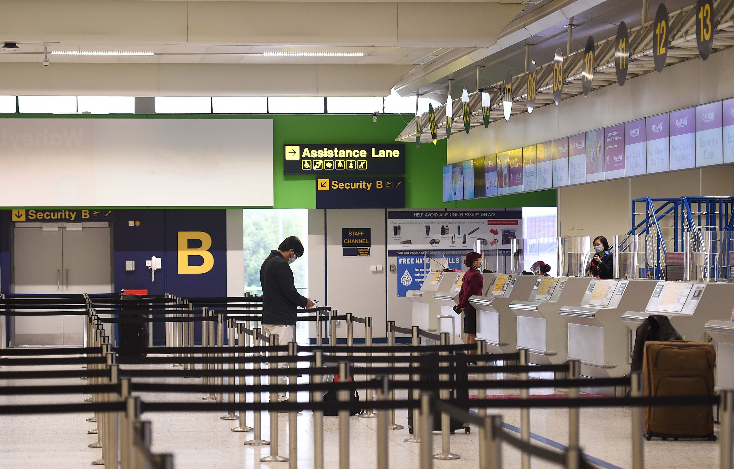 Passengers wearing PPE wait at a nearly deserted check-in desk in the Manchester Airport departure hall, in northern England, on May 11.