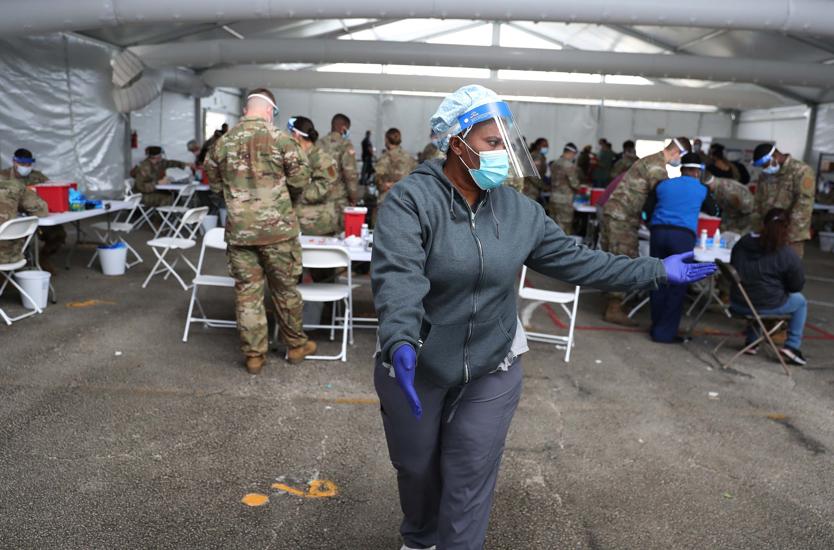 A health care worker directs people at a vaccination site in North Miami, Florida, on March 10.