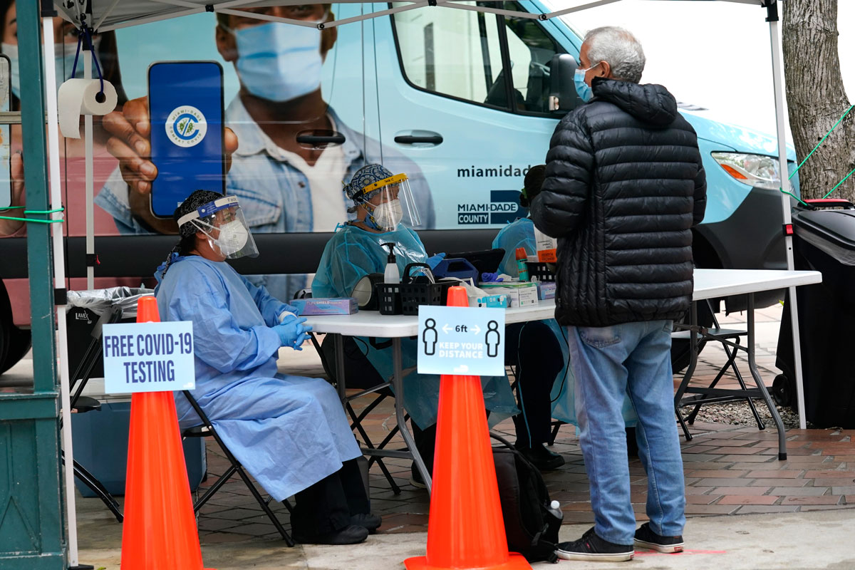 Health care workers offer free COVID-19 testing from a Miami-Dade County mobile van outside of an early voting site on Monday, October 19. in Miami.