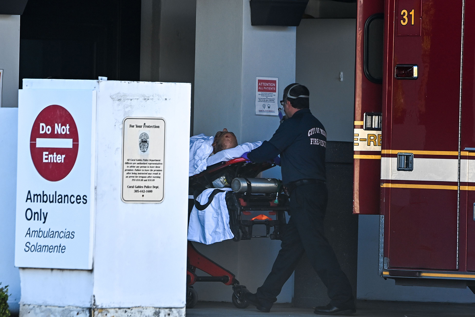 A medic transfers a patient on a stretcher from an ambulance outside of Emergency at Coral Gables Hospital where Coronavirus patients are treated in Coral Gables near Miami, Florida on December 10.