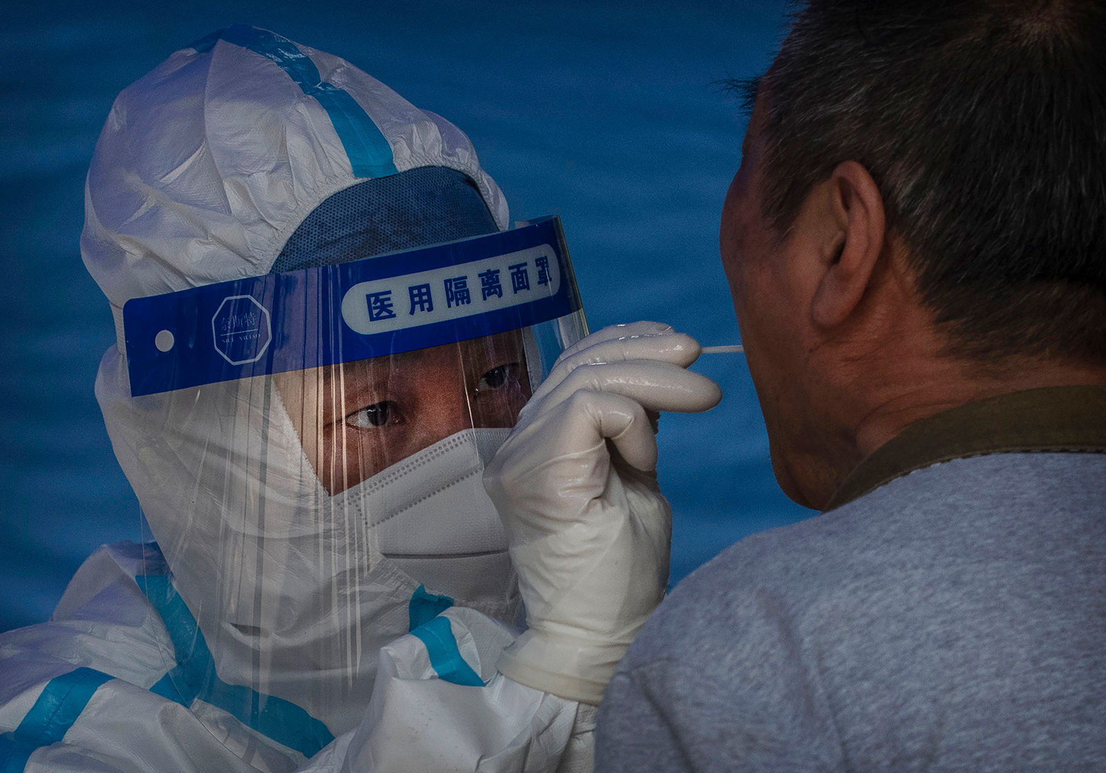 An epidemic control worker wears a protective suit as she performs a nucleic acid swab test for Covid-19 on a man at a government testing site on June 22, in Beijing, China.