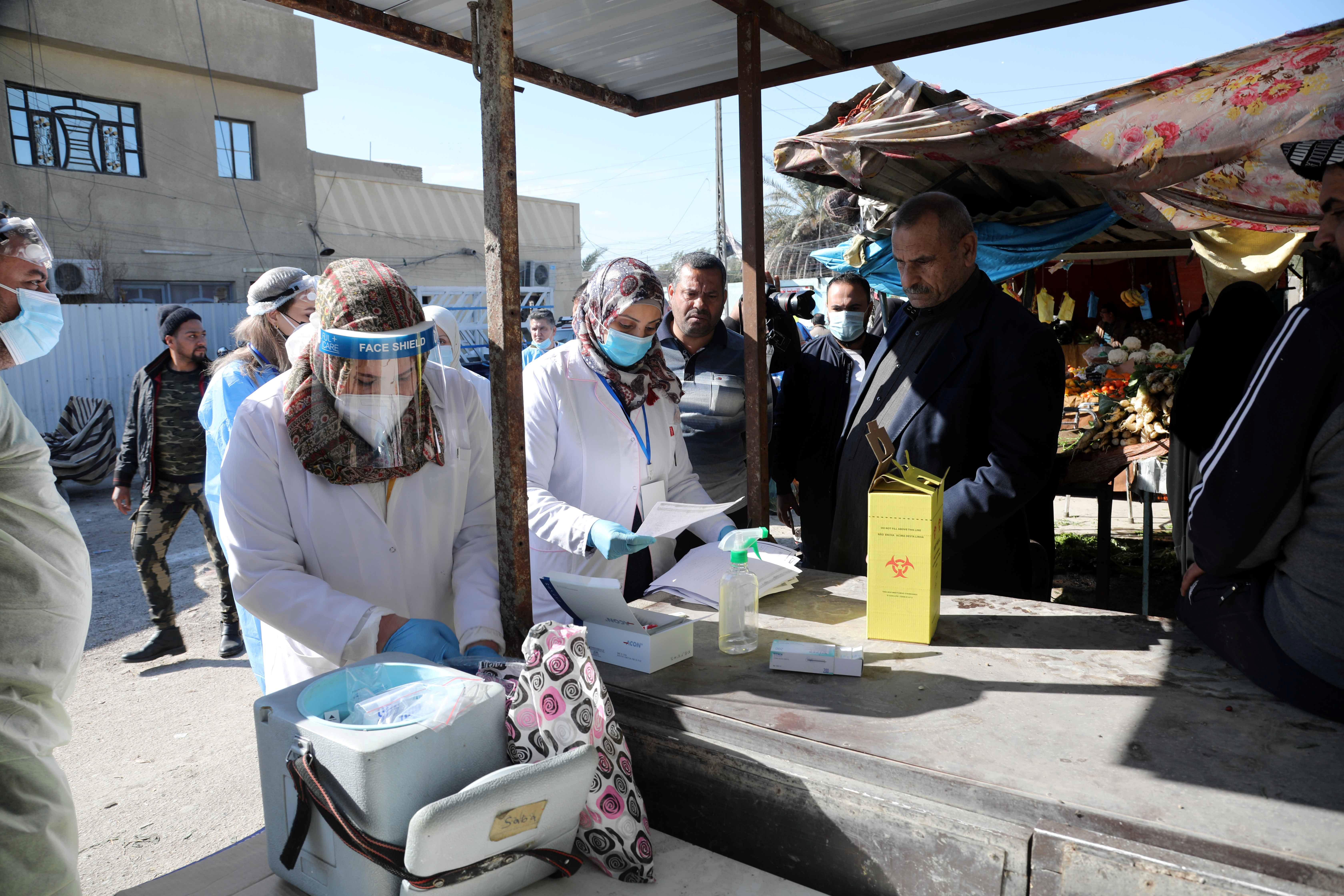 Health care workers are seen at a market in Baghdad, Iraq, during a campaign to detect coronavirus infections on January 31.