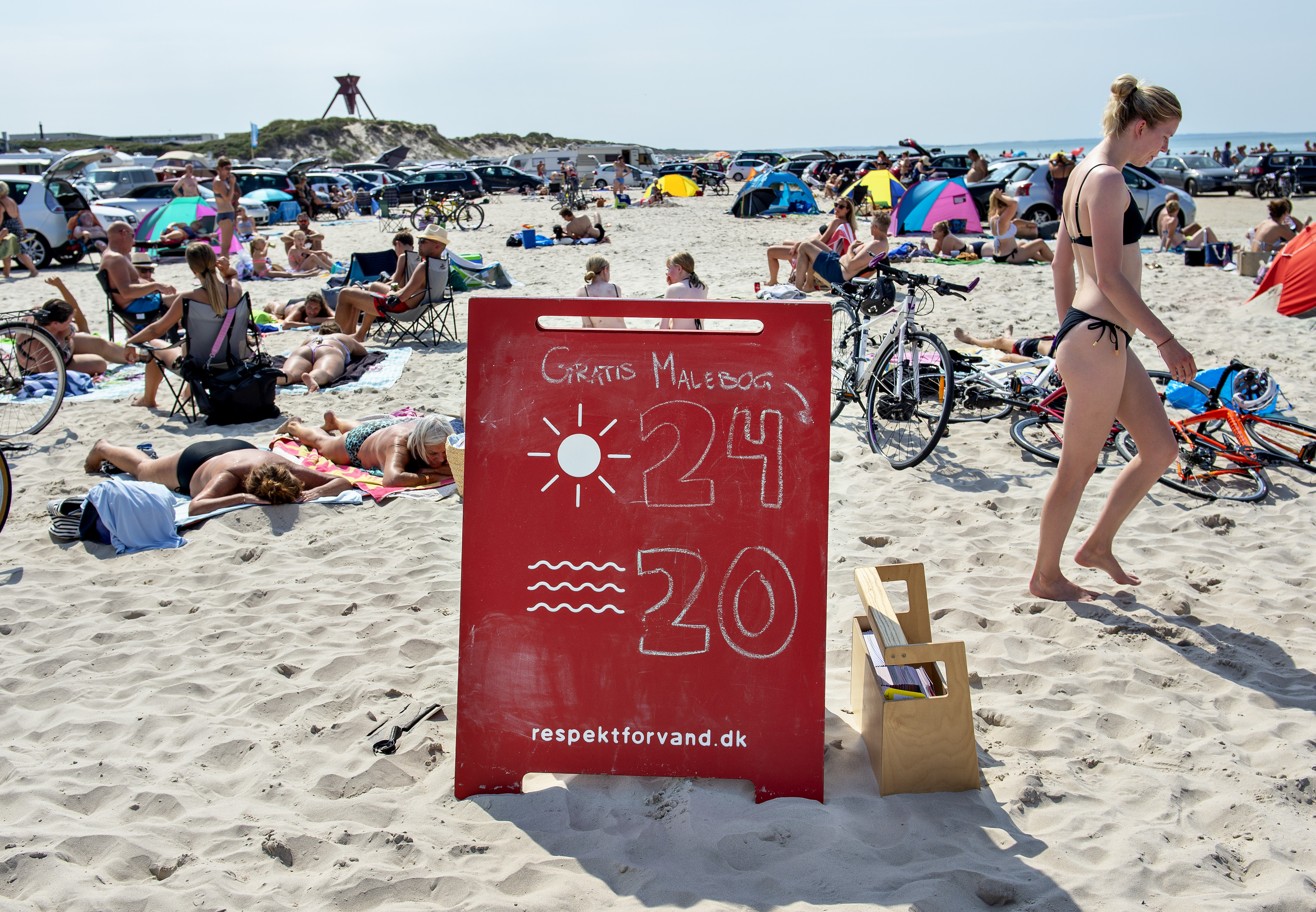 A stand shows air and water temperatures at a beach, which is packed with visitors enjoying the water of the North Sea on July 25, 2019 in Blokhus in Denmark.