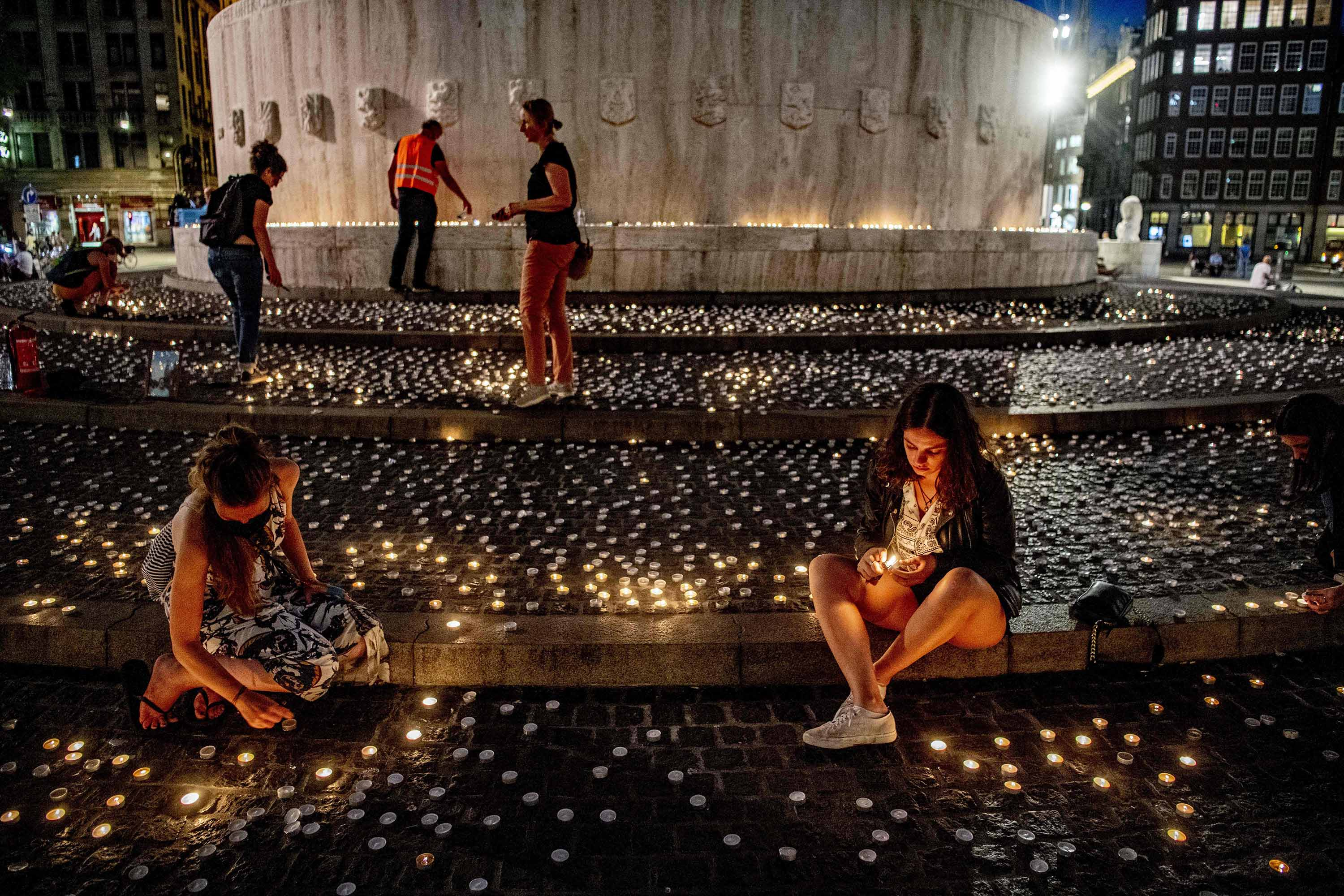 People light candles during a vigil for the victims of COVID-19 at the Dam, in Amsterdam, Netherlands, on August 6.
