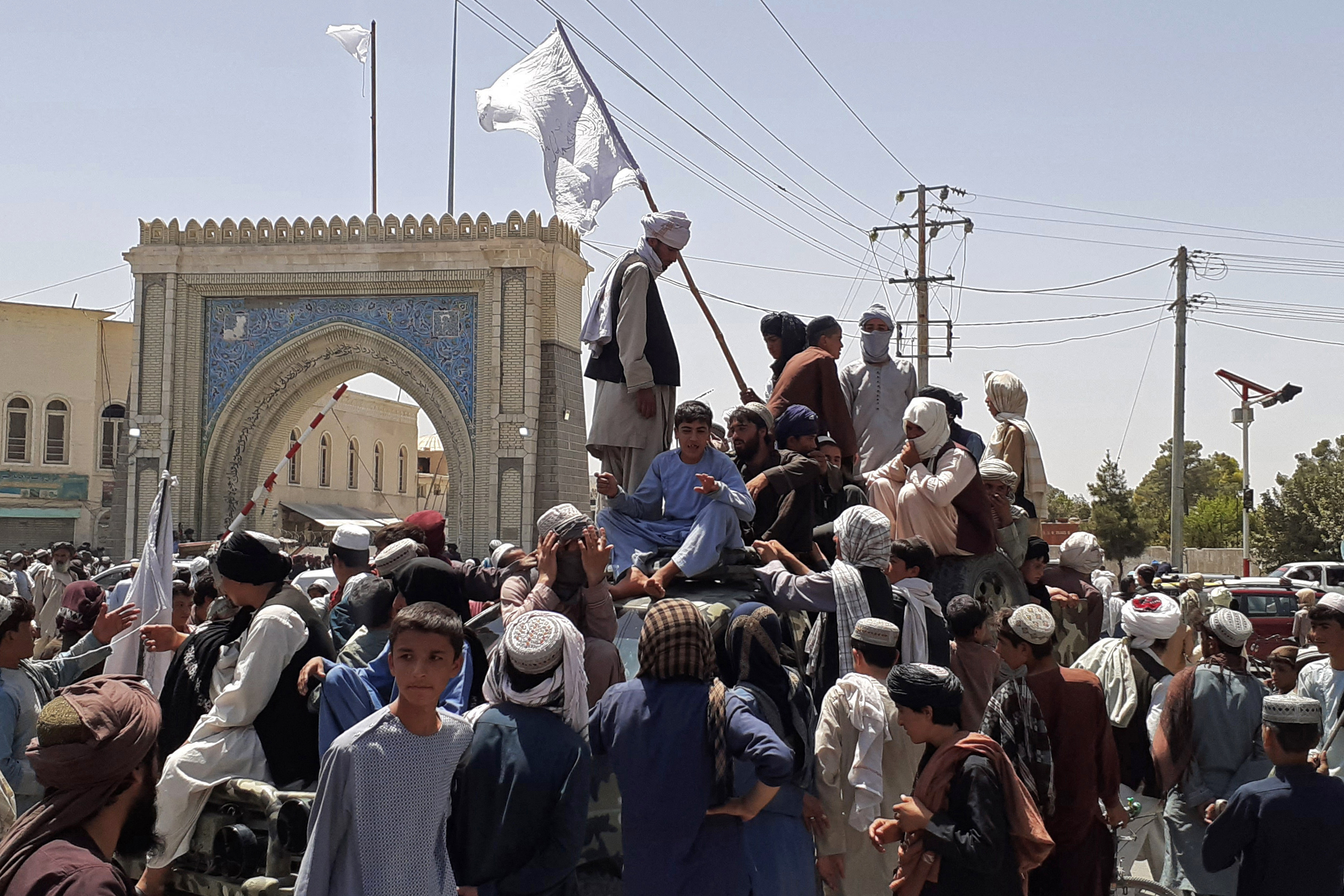 Taliban fighters stand on a vehicle in Kandahar on Friday, August 13.