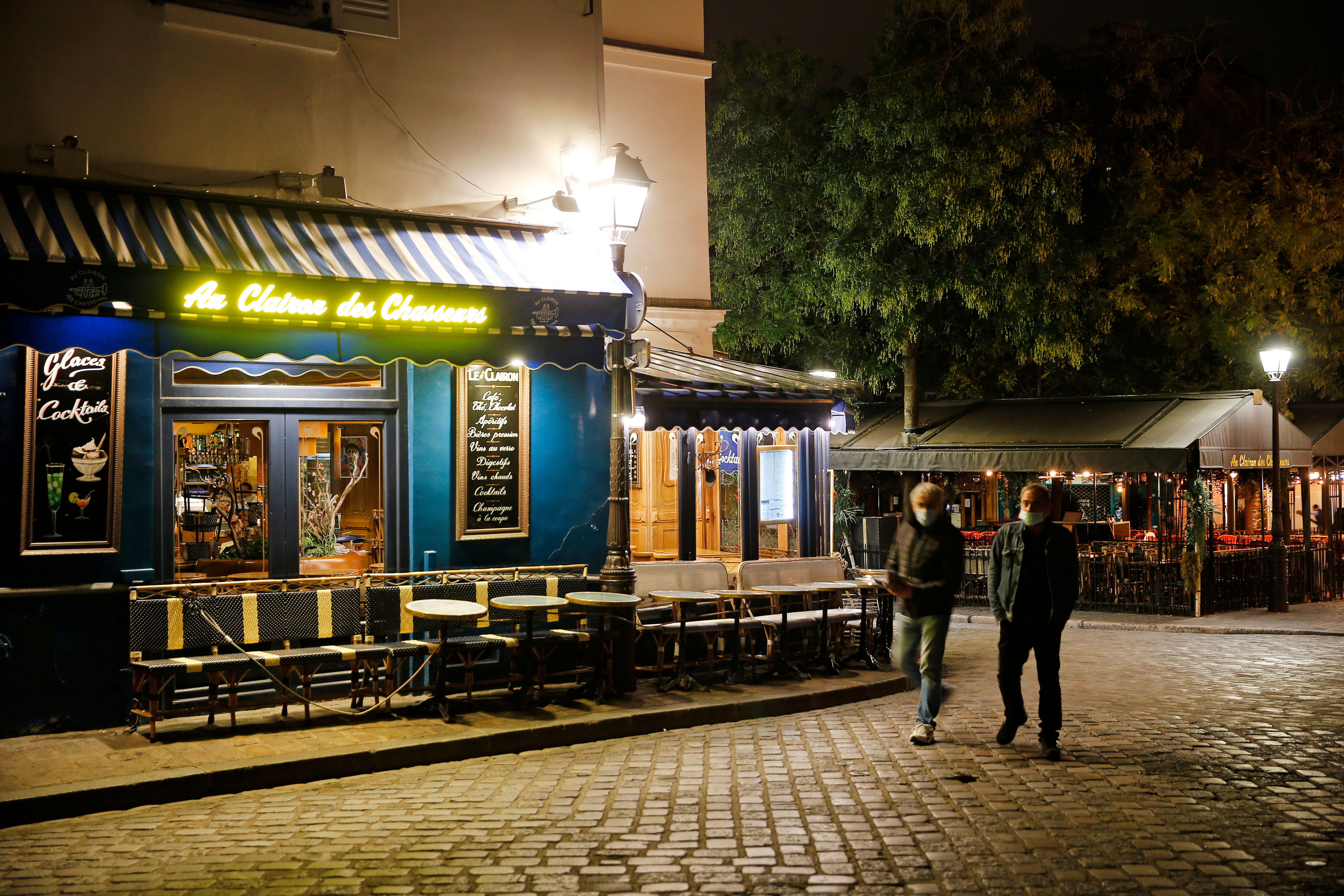 Men walk past empty restaurants at Place du Tertre in Paris on October 15.