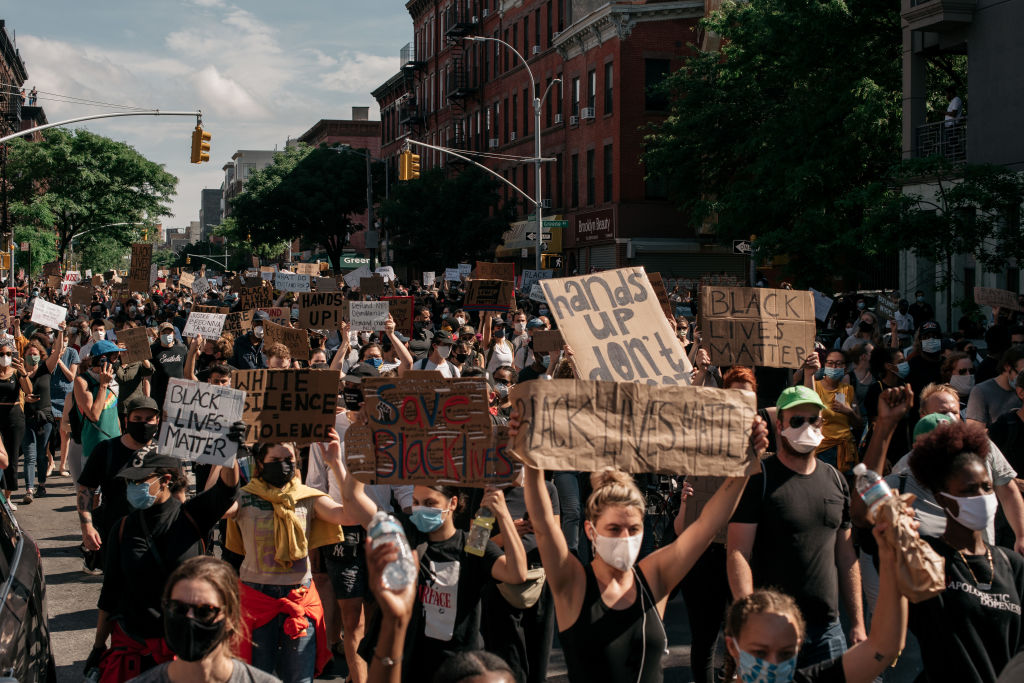 Demonstrators denouncing systemic racism in law enforcement and the killing of George Floyd by a Minneapolis Police officer raise signs and chant during a march through the borough of Brooklyn on June 3 in New York City.