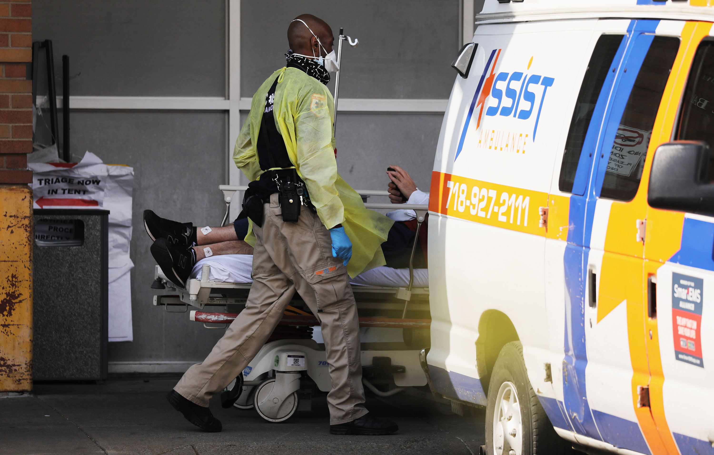 A medical worker transports a patient at a coronavirus intake area at Maimonides Medical Center on April 12, in the Brooklyn borough of New York City.