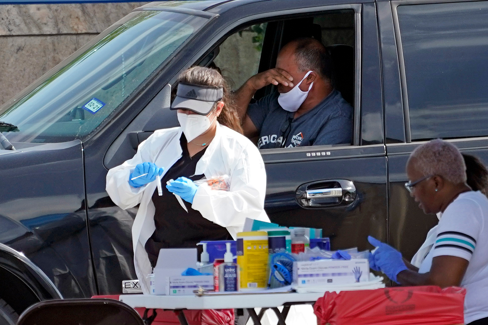 A patient reacts after a healthcare worker collected a sample at a United Memorial Medical Center Covid-19 testing site on July 16, in Houston.