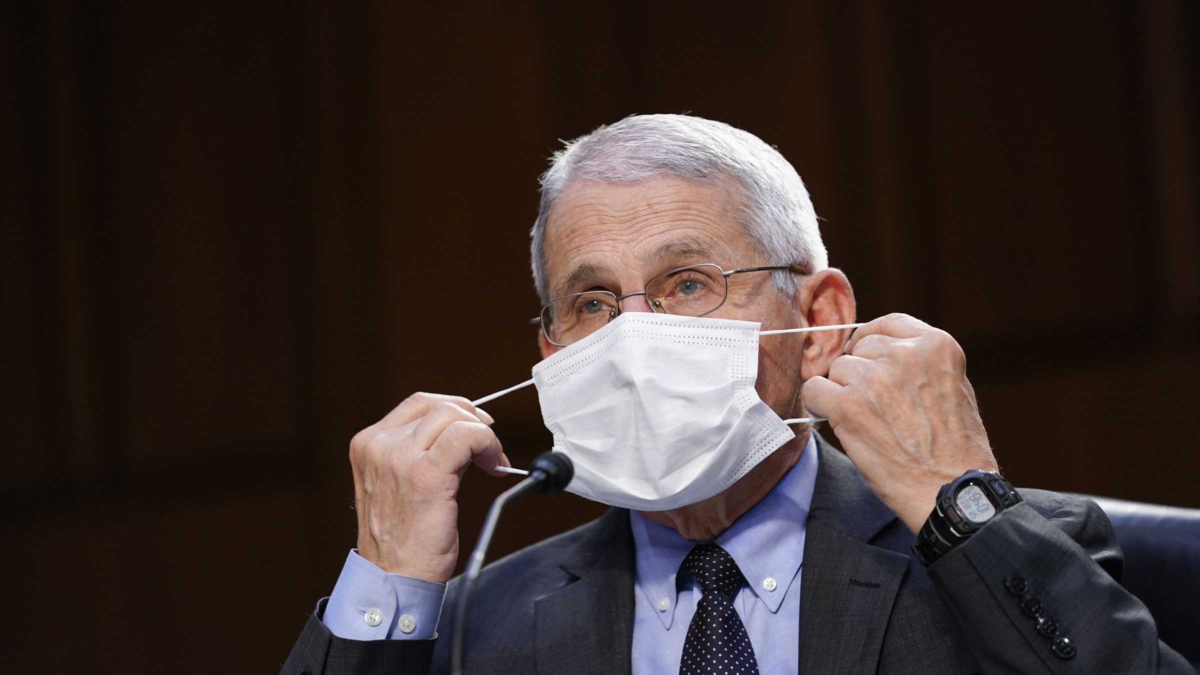 Dr. Anthony Fauci adjusts his mask during a Senate committee hearing in March.