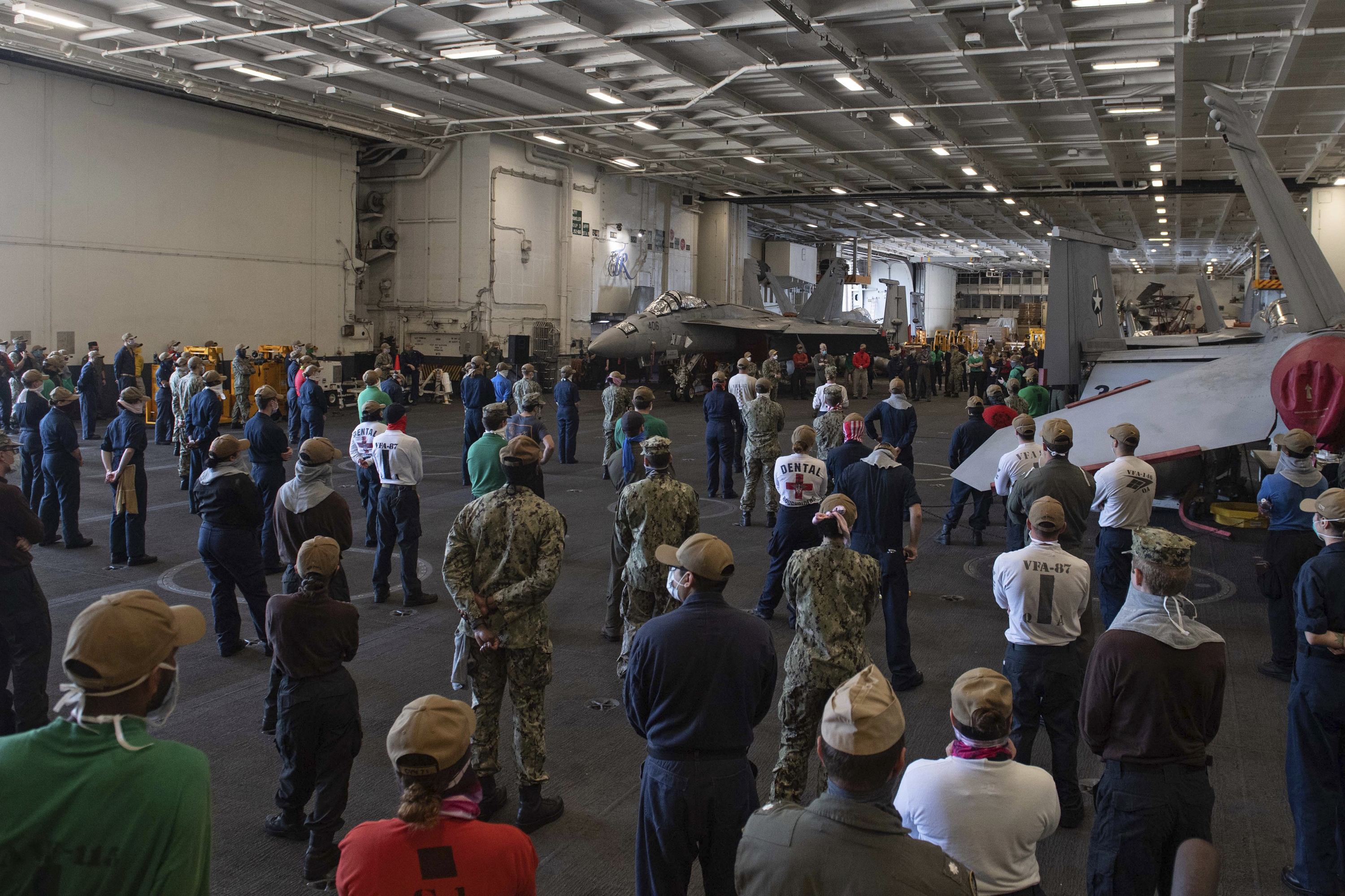 In this photo taken on April 7 and provided by the US Navy, sailors and staff assigned to the aircraft carrier USS Theodore Roosevelt listen as Vice Adm. William Merz, commander of the US 7th Fleet, answers questions during a visit to the ship at Naval Base Guam.
