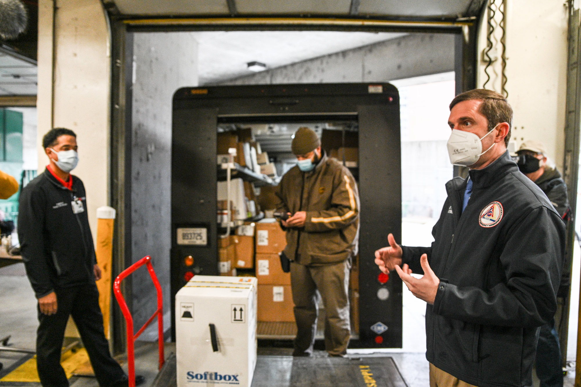 Kentucky Governor Andy Beshear, right, speaks to the media as Byron Bishop, a UPS driver, scans a delivered COVID-19 vaccination package in a loading dock at University of Louisville Hospital on December 14 in Louisville, Kentucky.