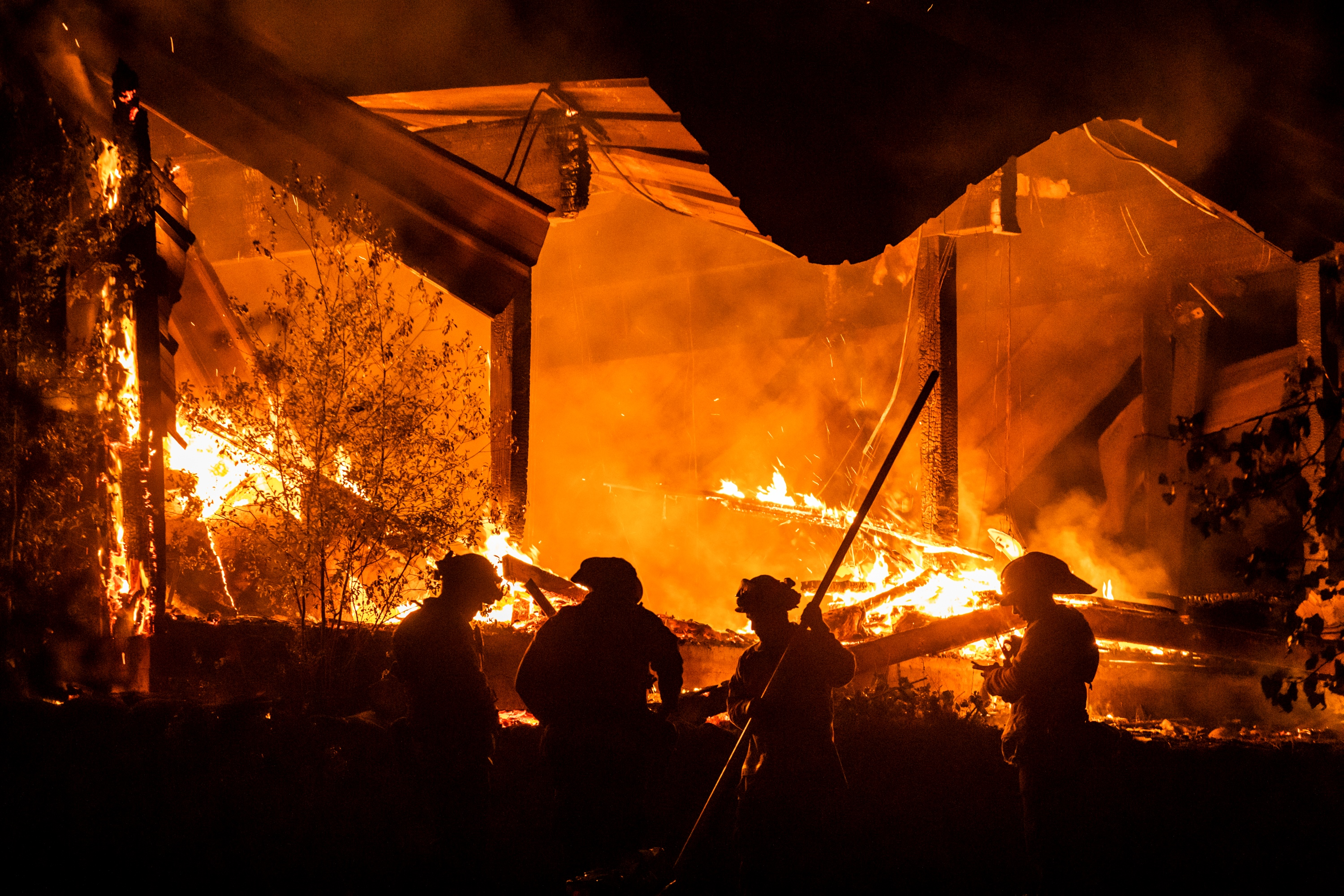 Firefighters tend to a structure lost during the Kincade fire on Tuesday.
