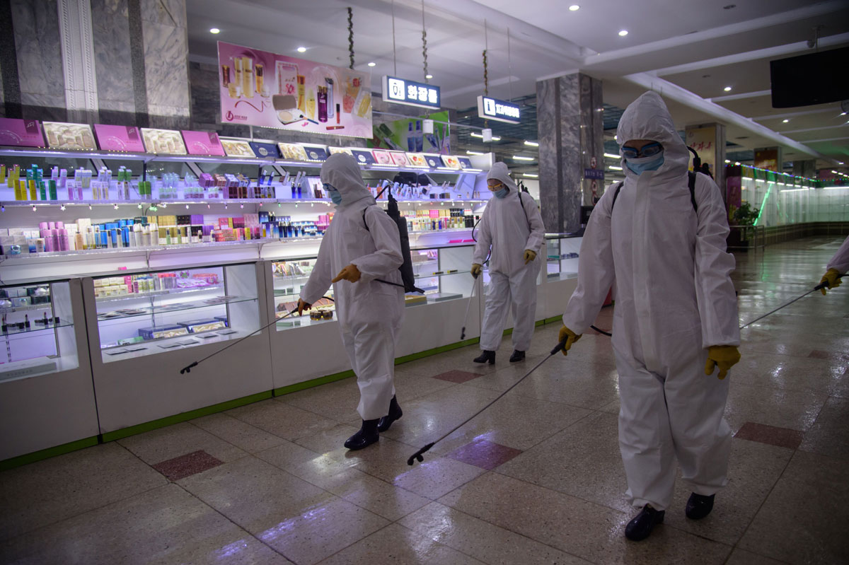Health workers spray disinfectant inside the Pyongyang Department Store No. 1 prior to opening for business in Pyongyang, North Korea on December 28, 2020.