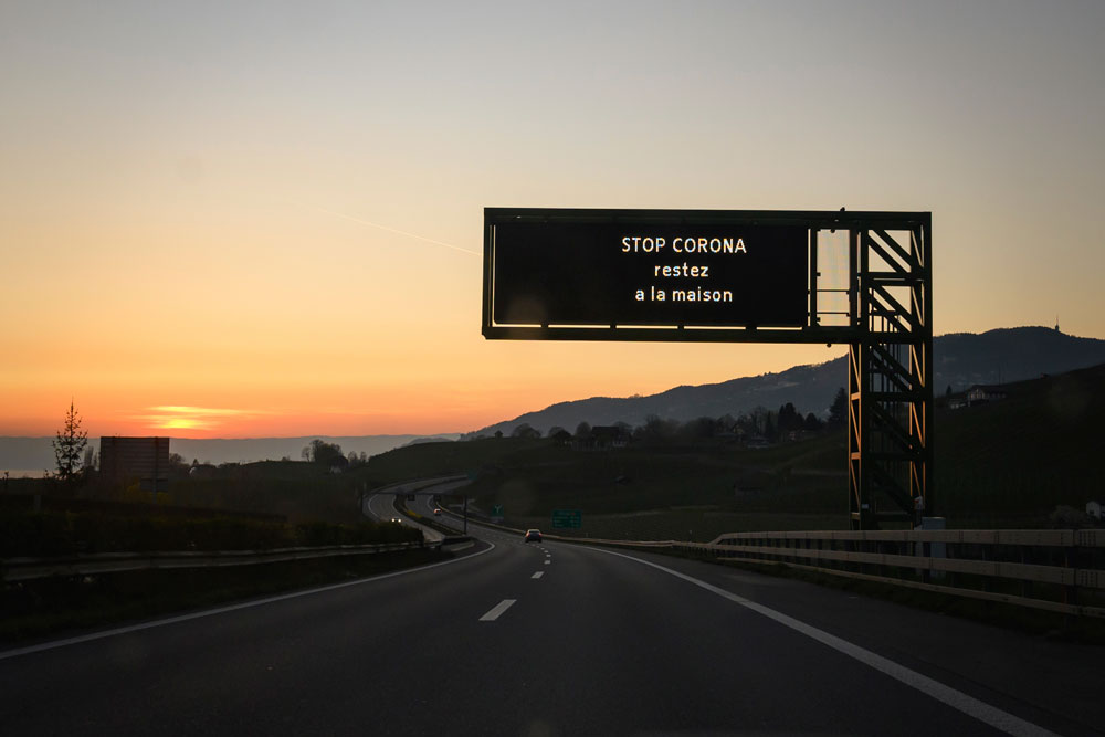 """A traffic board reading in French """"Stop corona, stay home"""" is seen at sunset on a motorway in Switzerland's municipality of Montreux on April 4."""