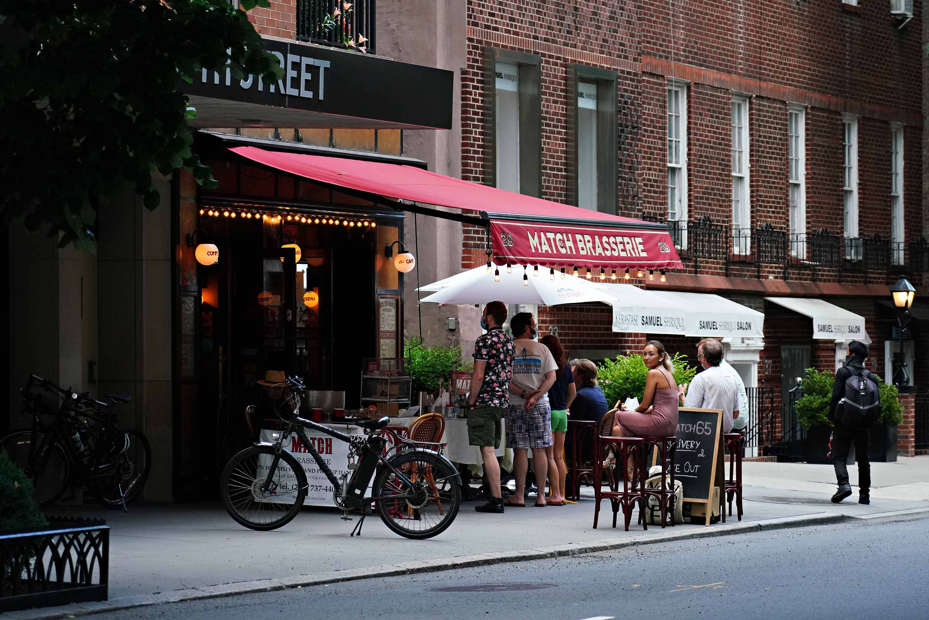A restaurant in New York serves drinks to customers outside on June 20.