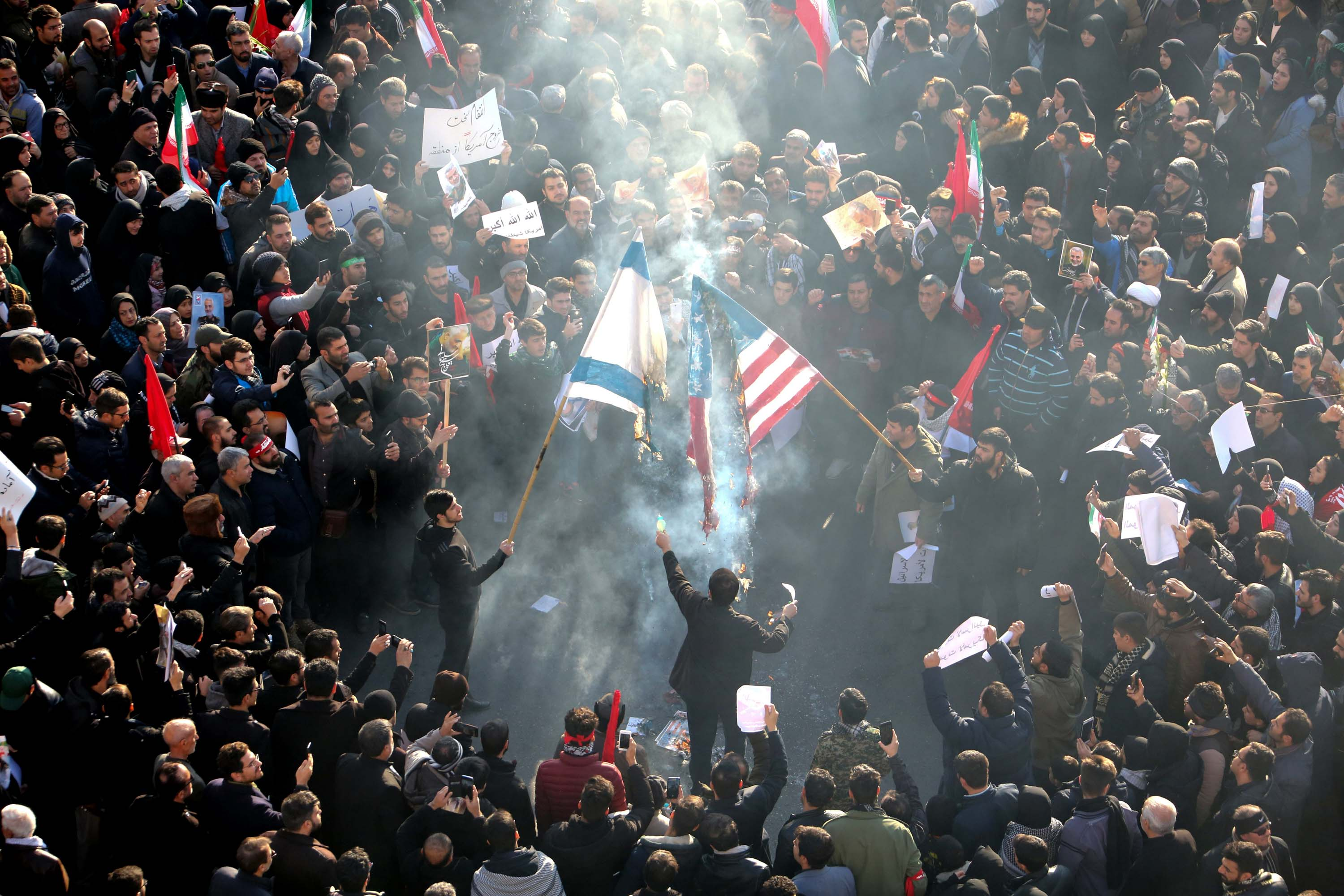 Iranians set a US and Israeli flag on fire during the funeral procession.