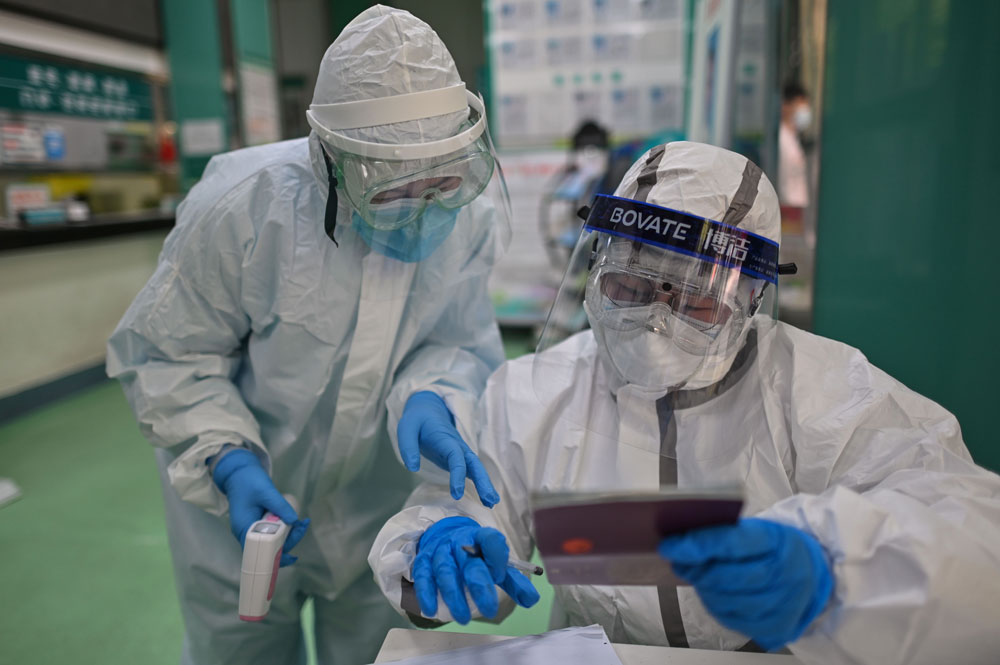 Medical workers check information as they take swab samples from people to be tested for the coronavirus in Wuhan, in China's central Hubei province on April 16.