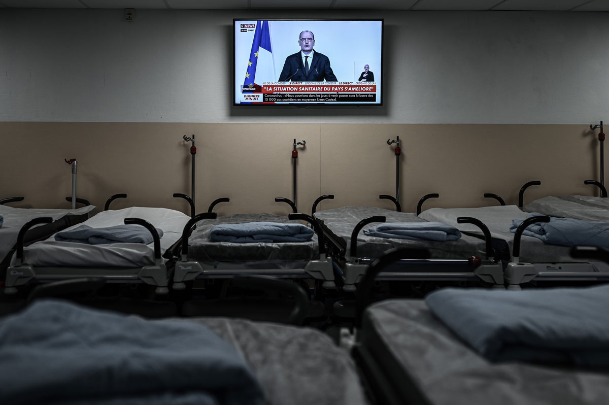 A television above empty beds at the Polyclinique Jean Villar private hospital in Bruges, France broadcasts French Prime Minister Jean Castex's press conference outlining the country's plans for deploying the coronavirus vaccine, on December 3.