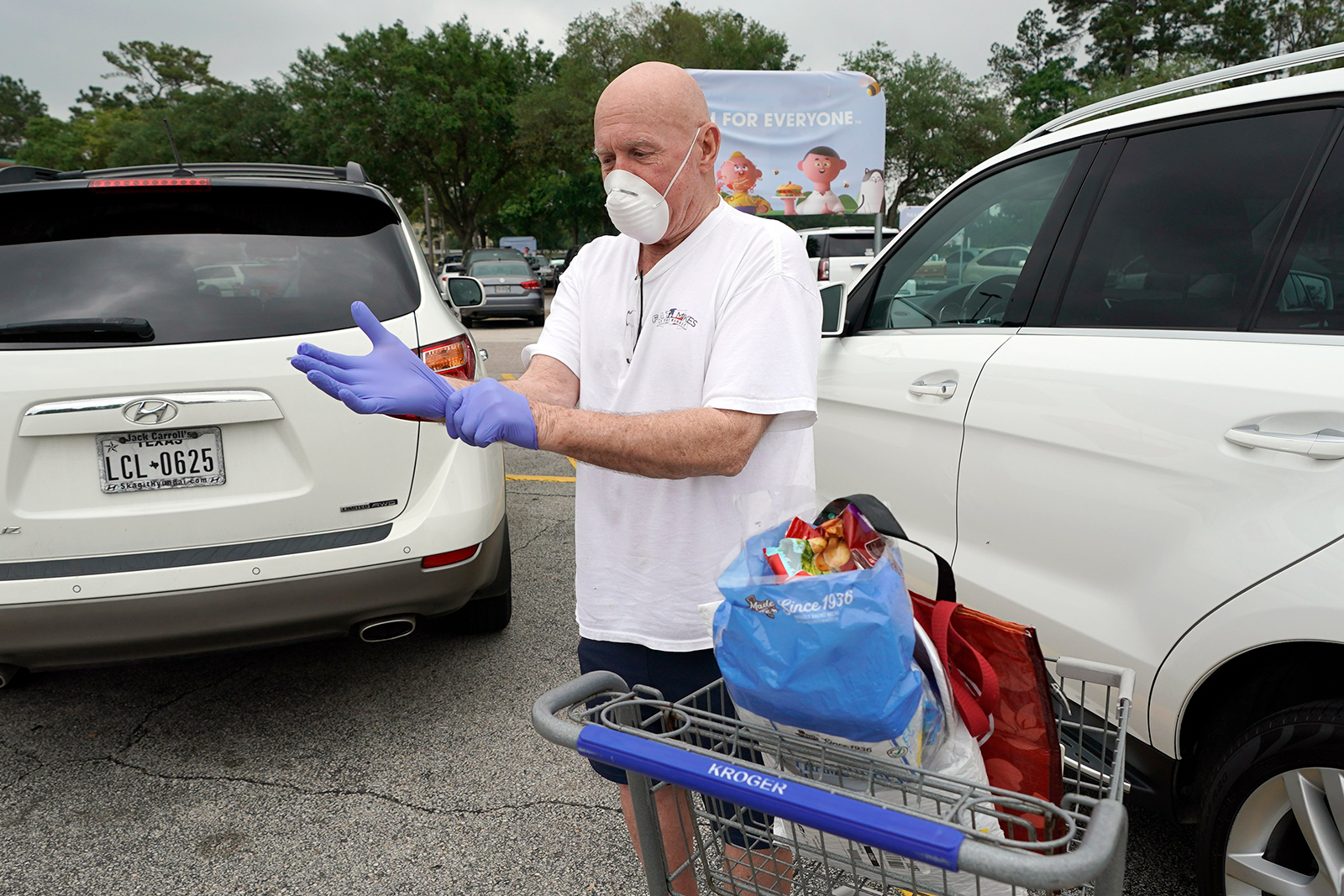 Gary Towler puts on gloves to protect against coronavirus, before entering a grocery store on April 22, in Spring, Texas.