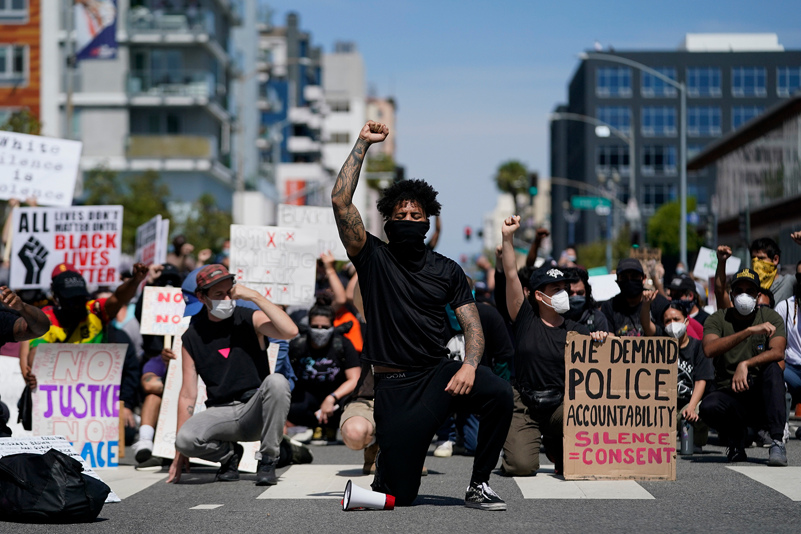 Demonstrators kneel in a moment of silence outside the Long Beach Police Department on Sunday, May 31 in Long Beach, California.
