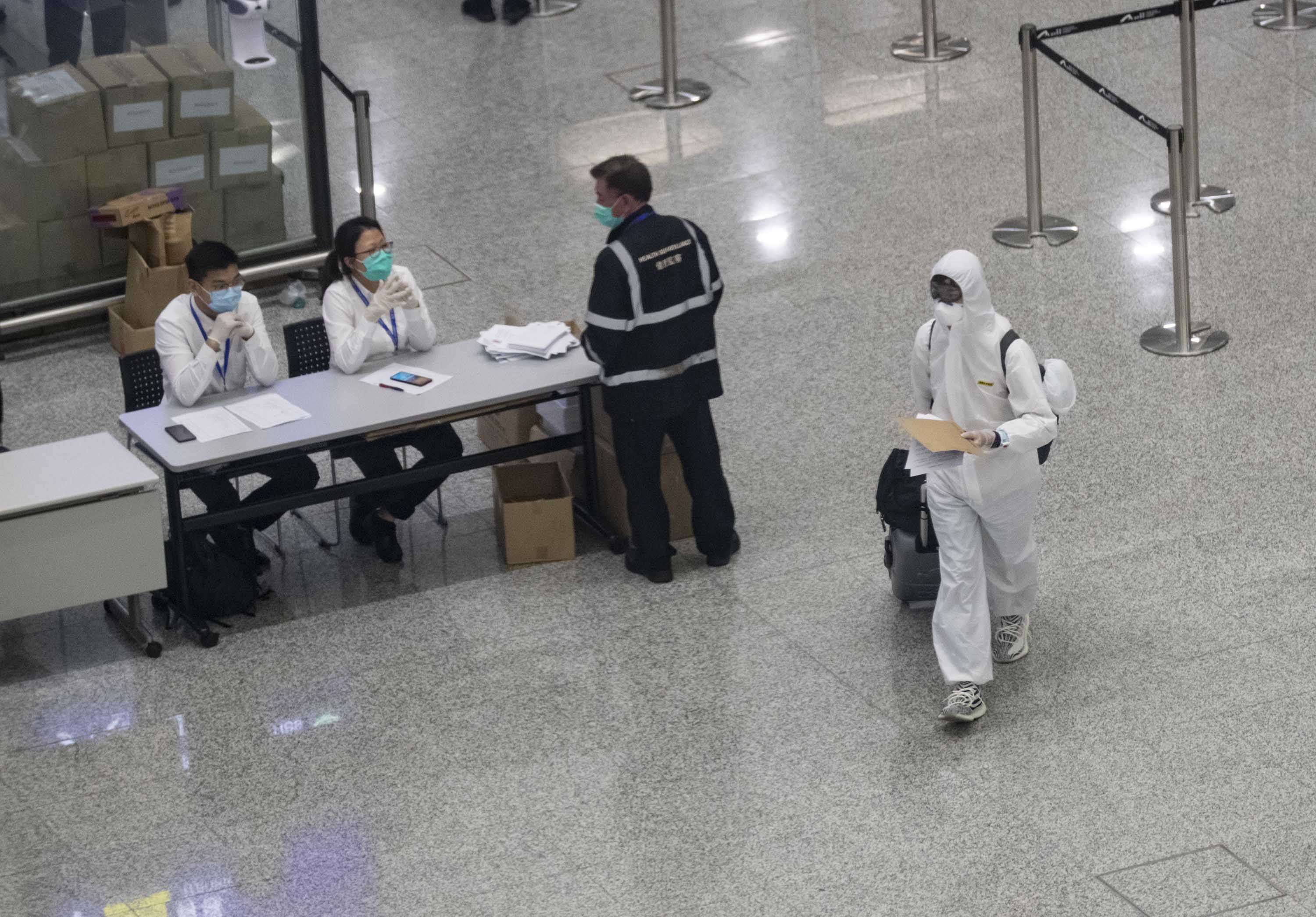 A passenger wearing a protective suite arrives at Hong Kong International airport on March 24.