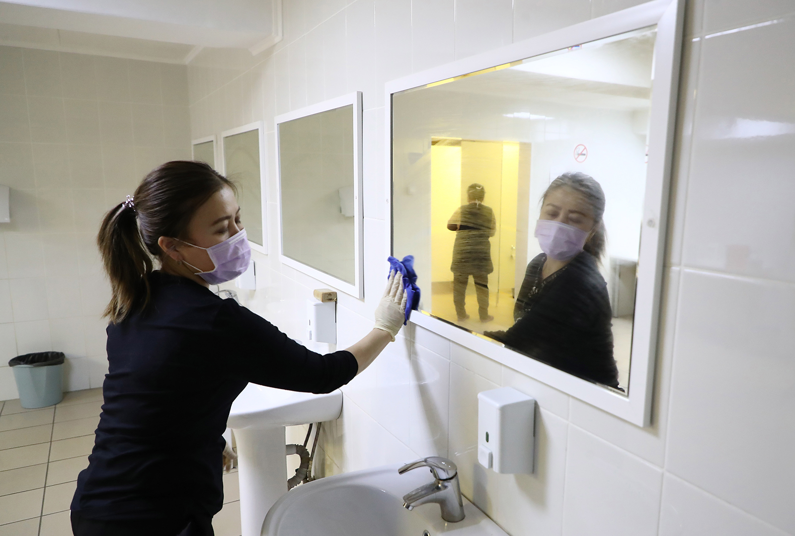 An employee disinfects mirrors in a bathroom at the Taganka Theatre in Moscow on March 17.