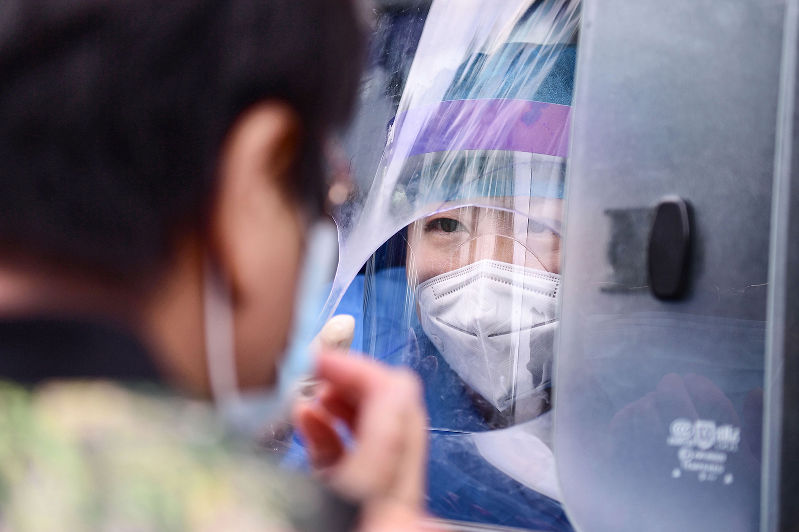 A health worker carries out a Covid-19 test on a resident in a testing vehicle in Shenyang in China's northeastern Liaoning province on July 29.