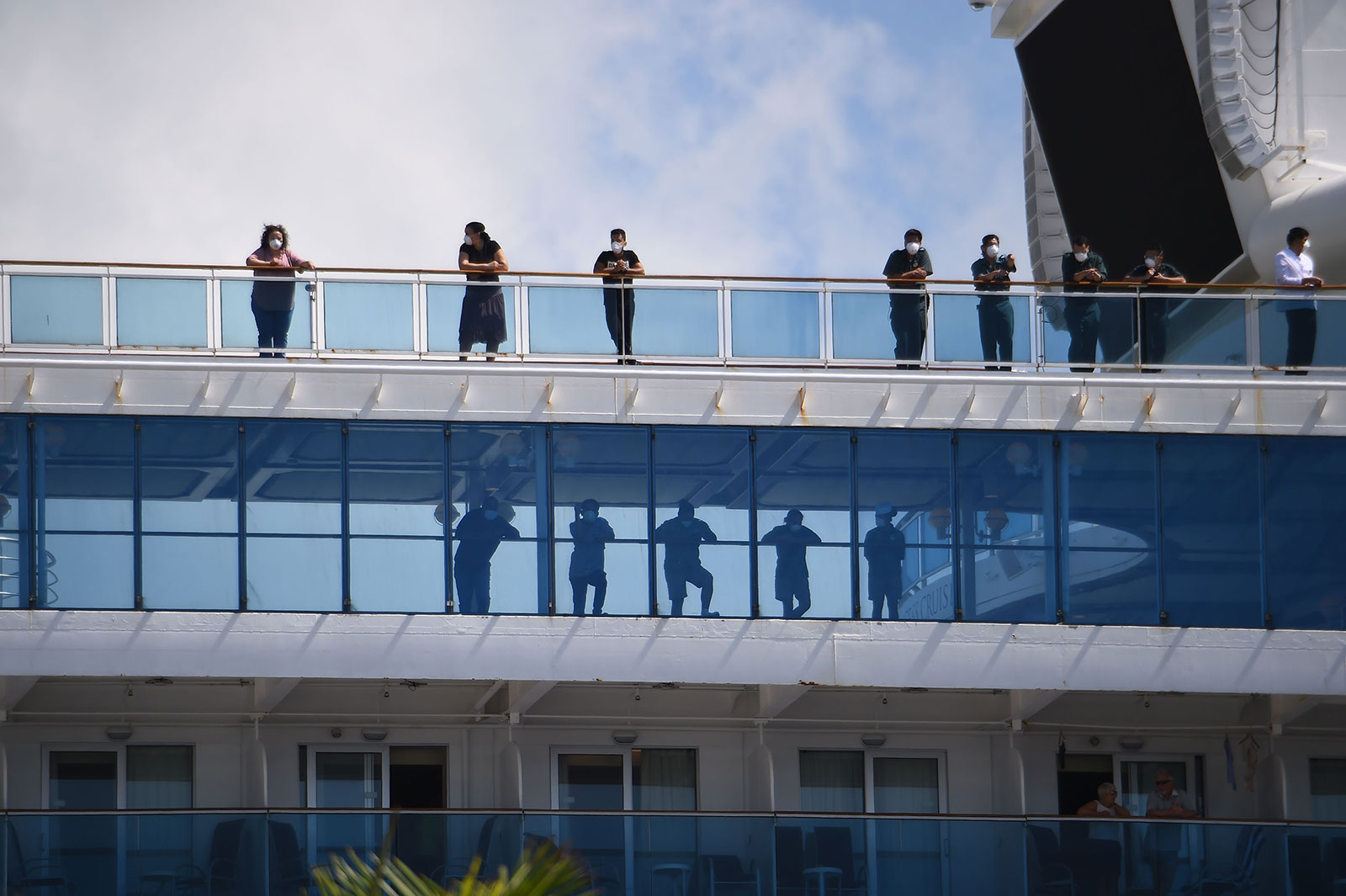 Passengers look out from the deck of the Coral Princess cruise ship as it docks in Miami, Florida, on April 4.