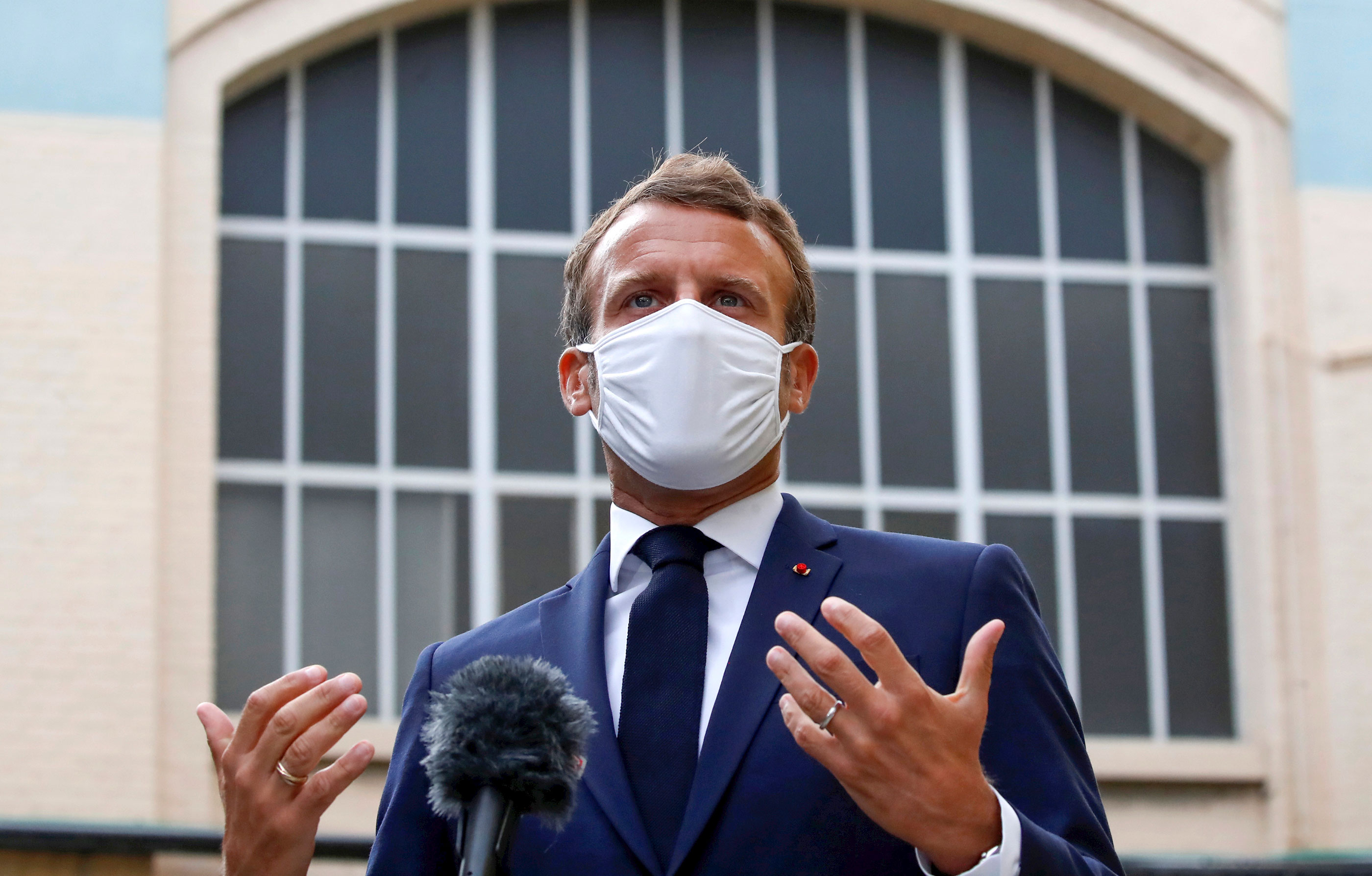 French President Emmanuel Macron speaks to the media as he visits a site of pharmaceutical group Seqens on August 28 in Paris, France.