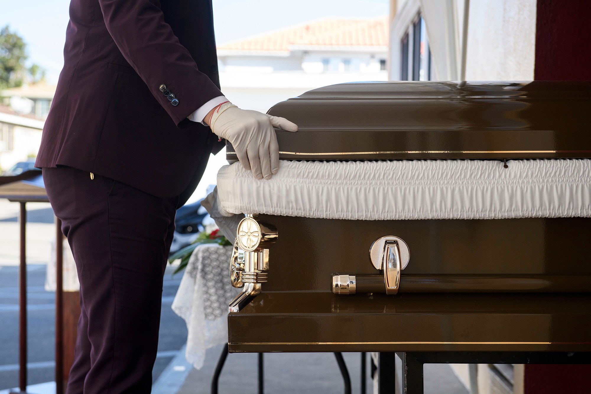 Funeral director Steven Correa moves the casket of Gilberto Arreguin Camacho, 58, in preparation for burial following his death due to Covid-19 at the Continental Funeral Home on December 31, in Los Angeles, California.