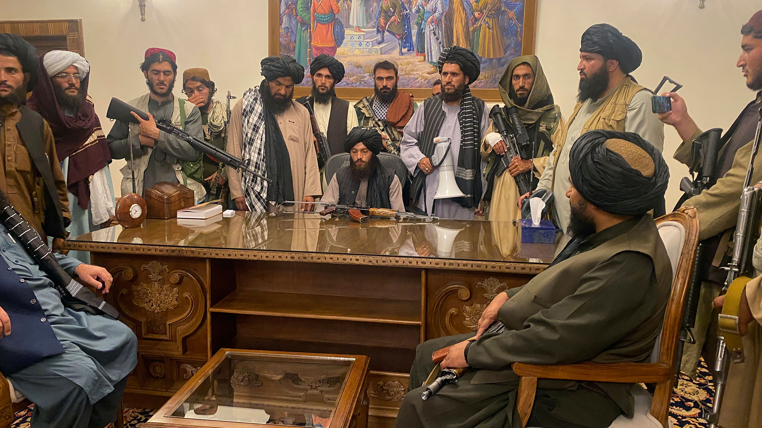 Taliban fighters sit inside the presidential palace in Kabul, Afghanistan, on Sunday, August 15.
