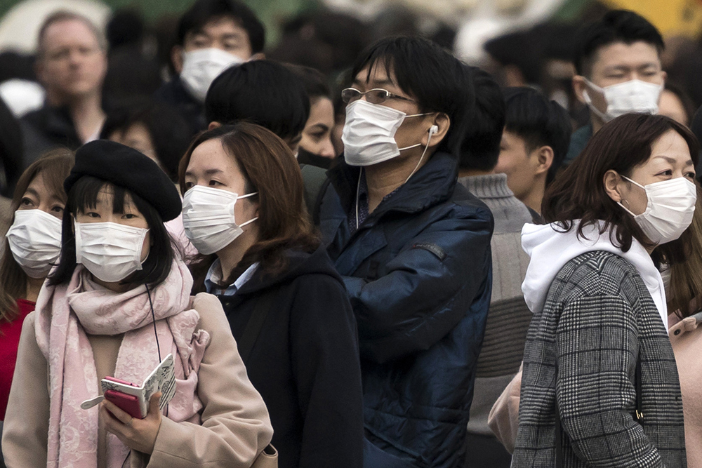 People wearing masks wait to cross a roadin the Shibuya district on February 2, 2020 in Tokyo.